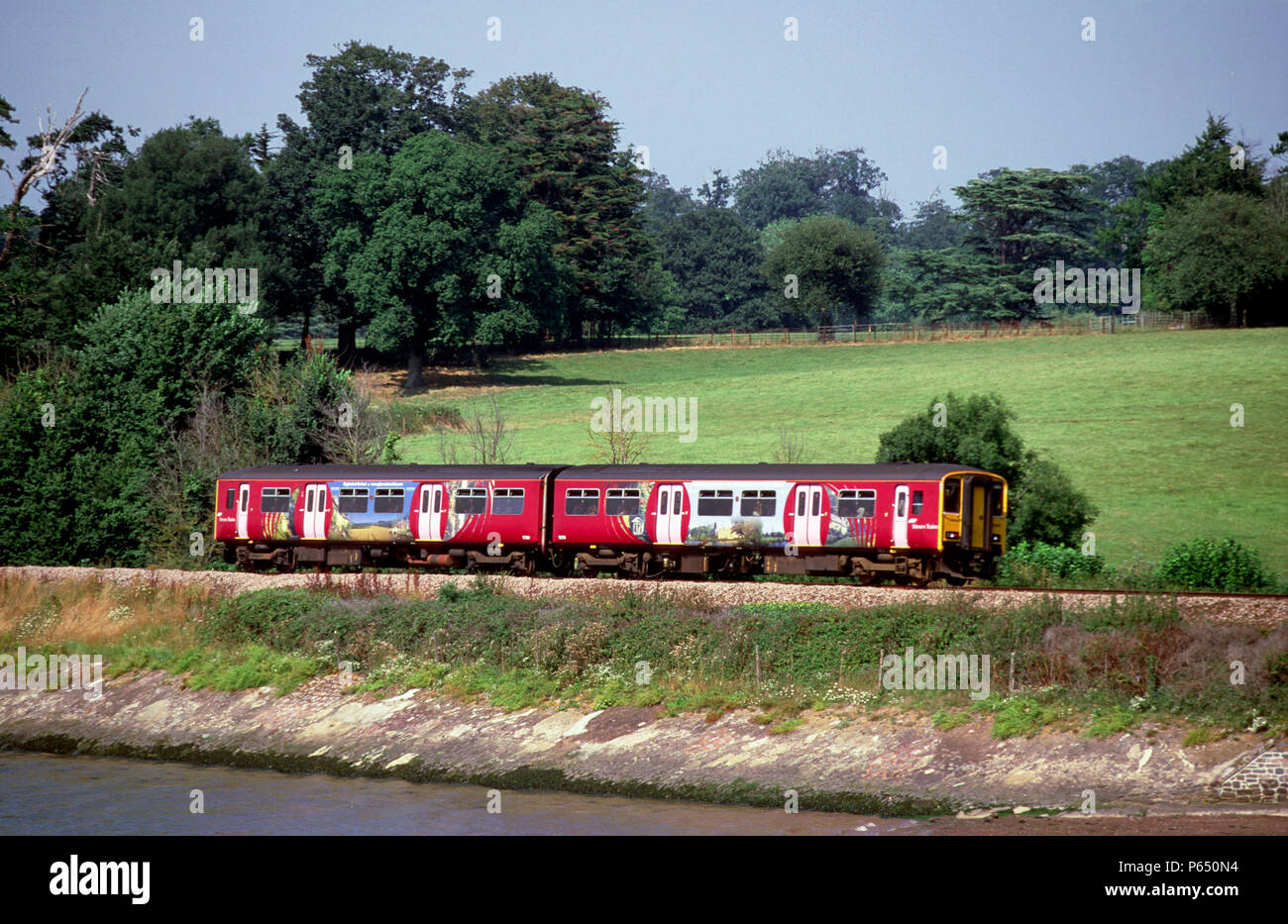 A brightly liveried Class 150/2 skirts the Devon coastline at Lympstone en route From Plymouth to Exmouth. August 2003. - Stock Image