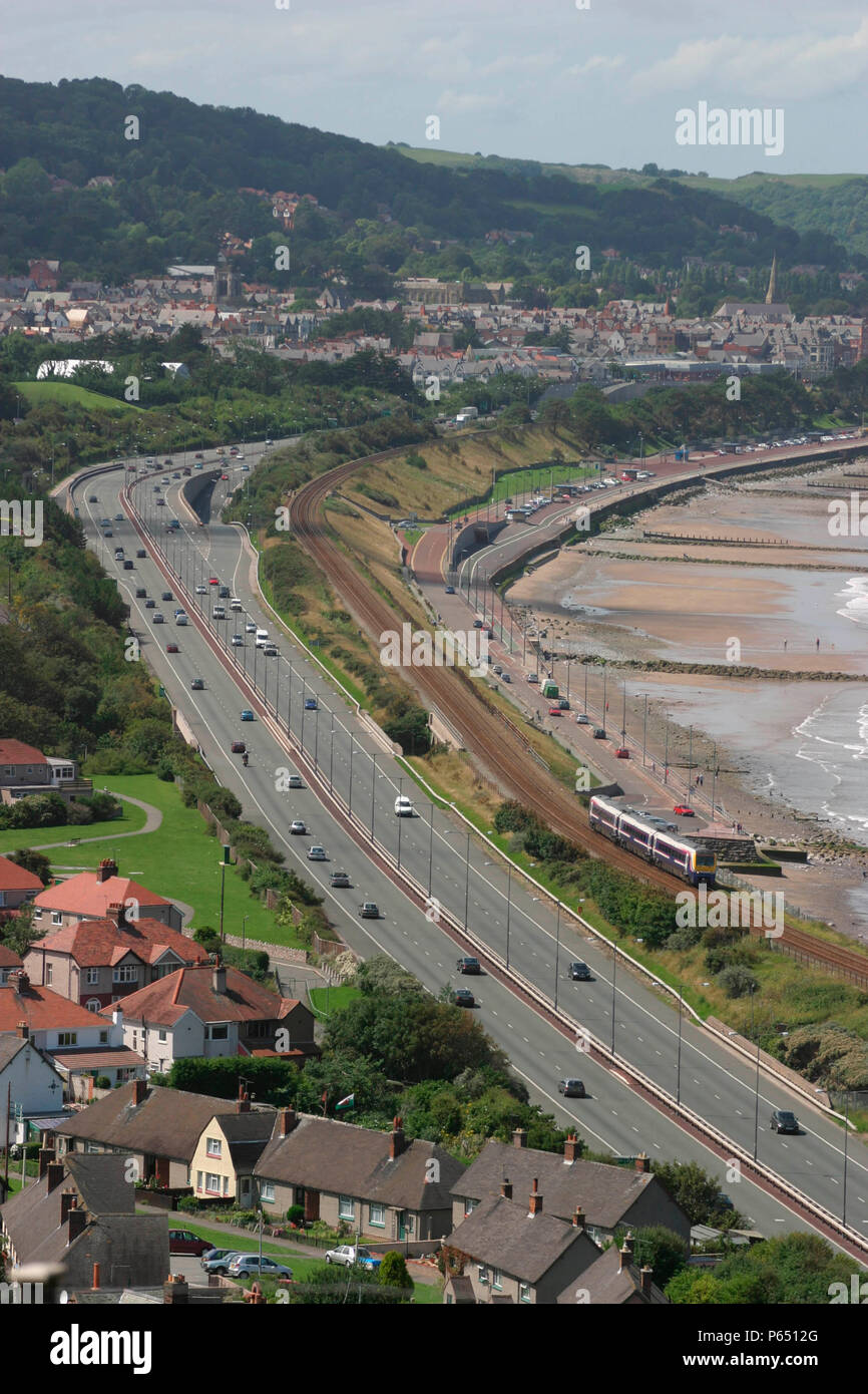 A First North Western Class 175 with a service from Holyhead runs alongside the A55 trunk road as it skirts the North Wales coast at Colwyn Bay. July  - Stock Image