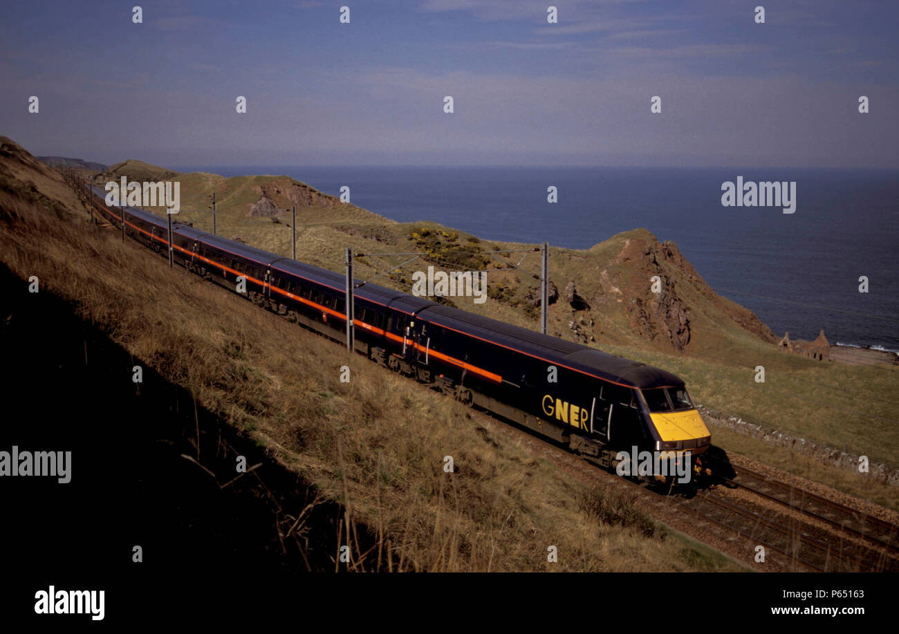 A GNER service heads north where the East Coast Main Line skirts the North Sea near Berwick upon Tweed. C 1998 - Stock Image