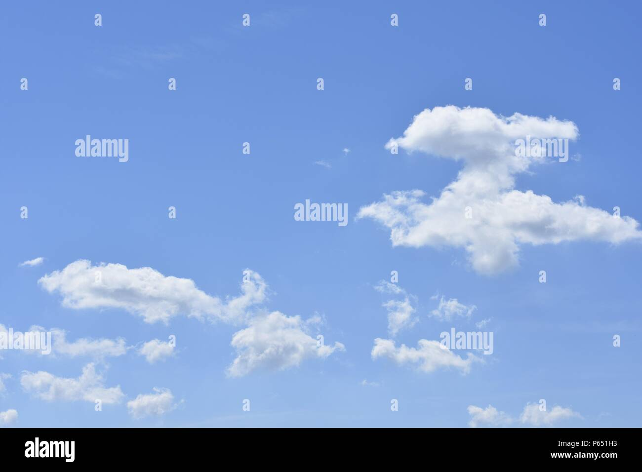 Blue sky with white clouds in different dreamy shapes - Stock Image