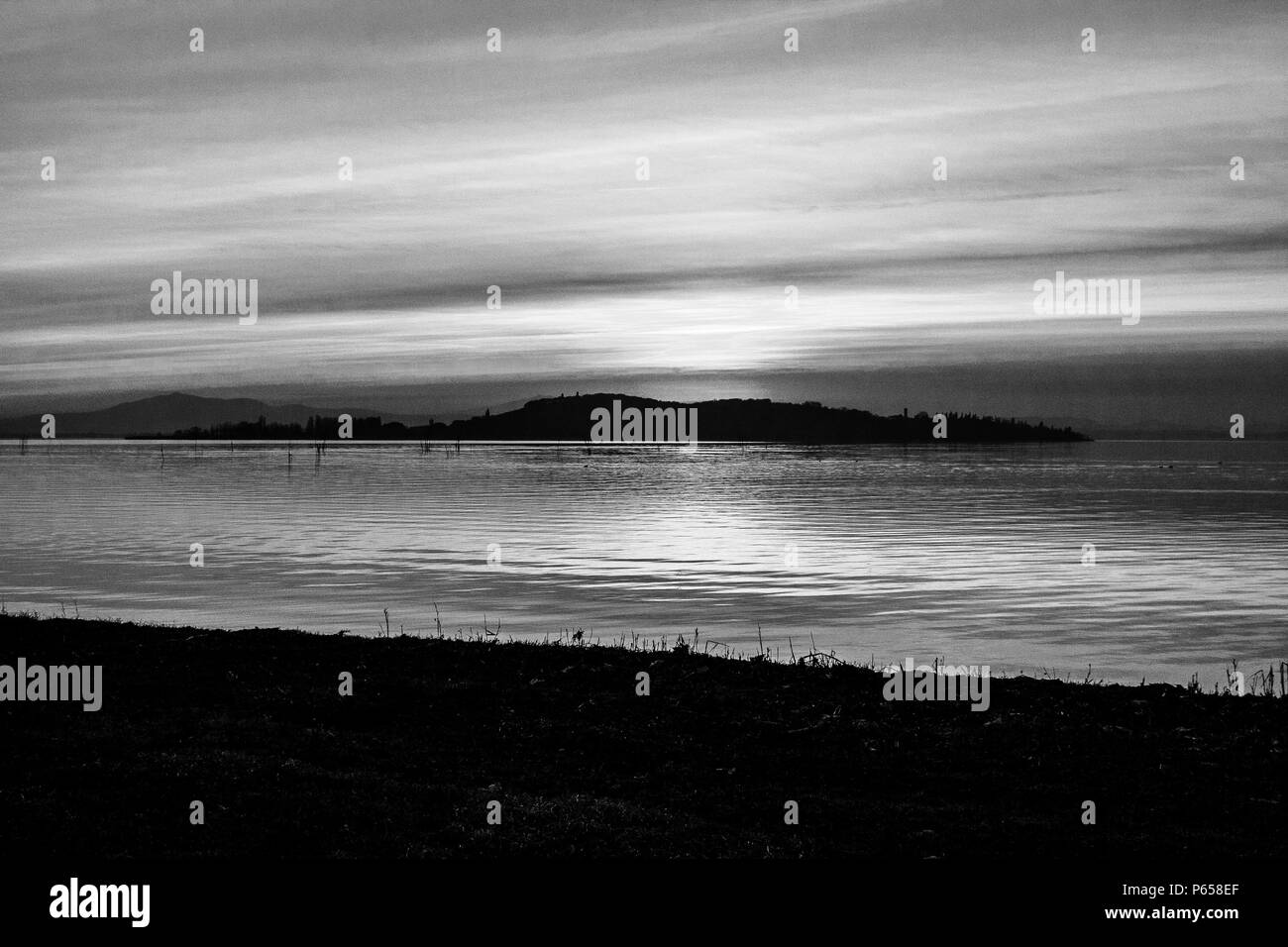 A shoot of a sunset over a lake, with many diagonal lines created by the clouds and the coastline - Stock Image
