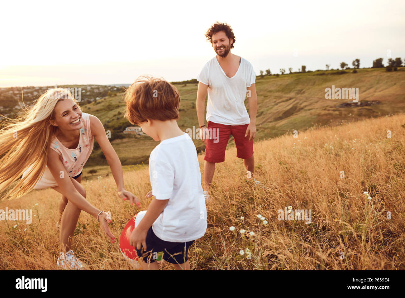 Happy family having fun playing at sunset in nature. - Stock Image