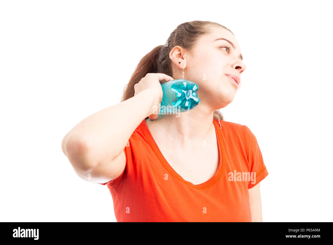 Sweating attractive young woman cooling with bottle of water touching her neck as summer hot temperature concept isolated on white background - Stock Image