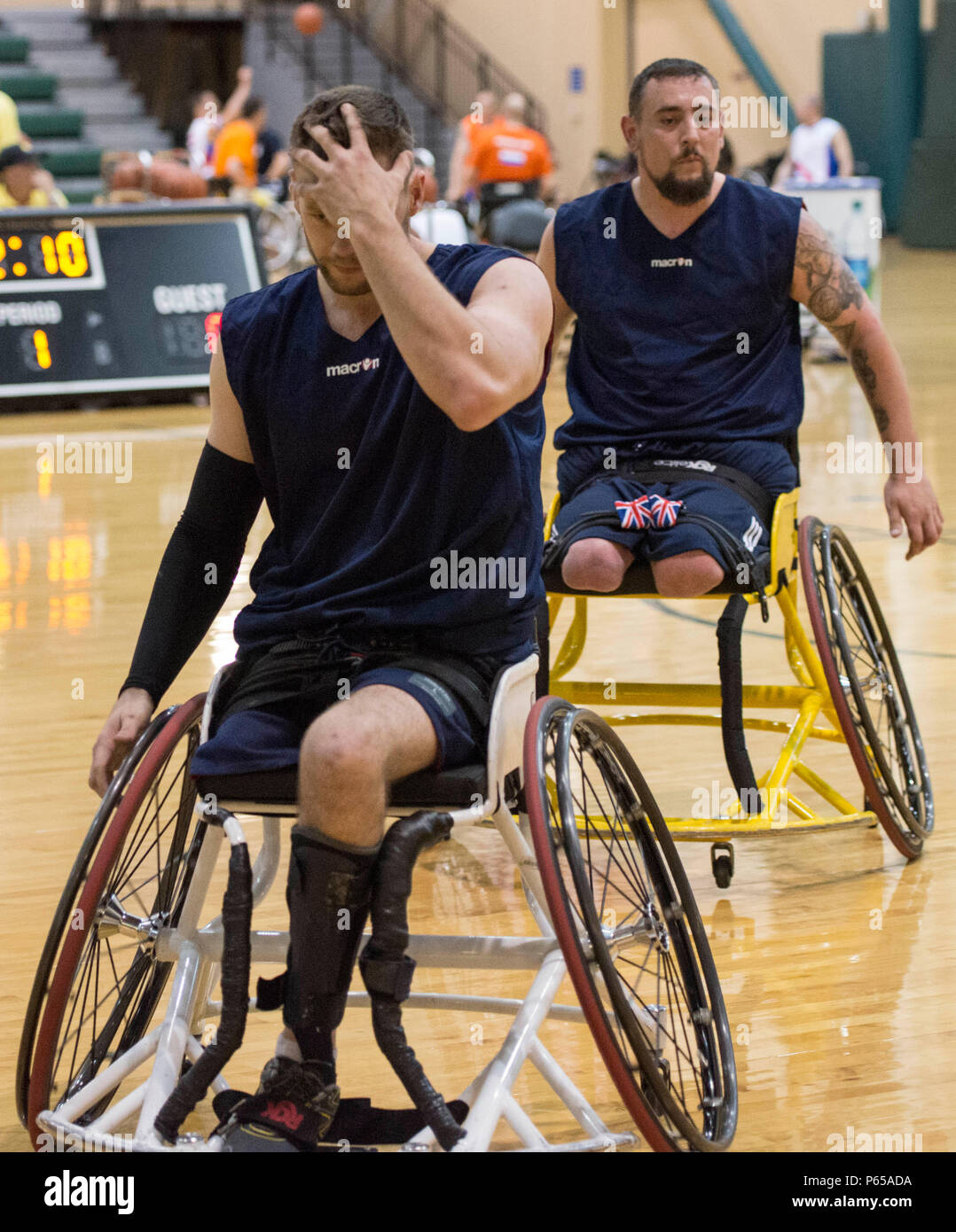 160505-F-WU507-024: British Army Pvt. Gareth Golightly (front) and British Army LCpl. Craig Winspear (both retired), leave the court as substitutions during a training game at the ESPN Wide World of Sports complex at Walt Disney World, Orlando, Fla., May 5, 2016. Team U.K. is one of 15 nations competing in the Invictus Games, which was created by Prince Harry, a former British Army officer and son of Prince Charles, the Prince of Wales. (U.S. Air Force photo by Senior Master Sgt. Kevin Wallace/RELEASED) - Stock Image