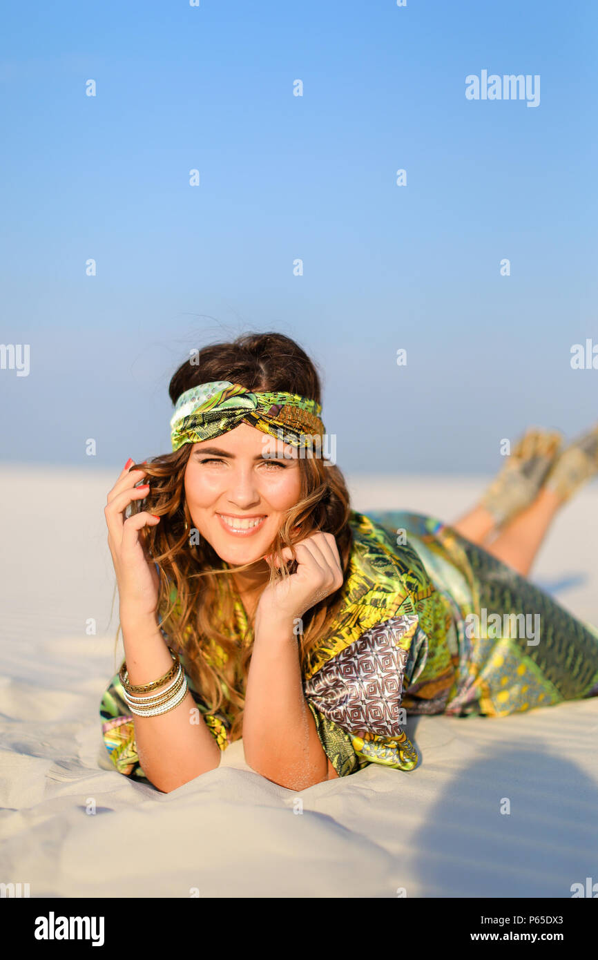 Young woman wearing green beach robe lying on white sand. Stock Photo