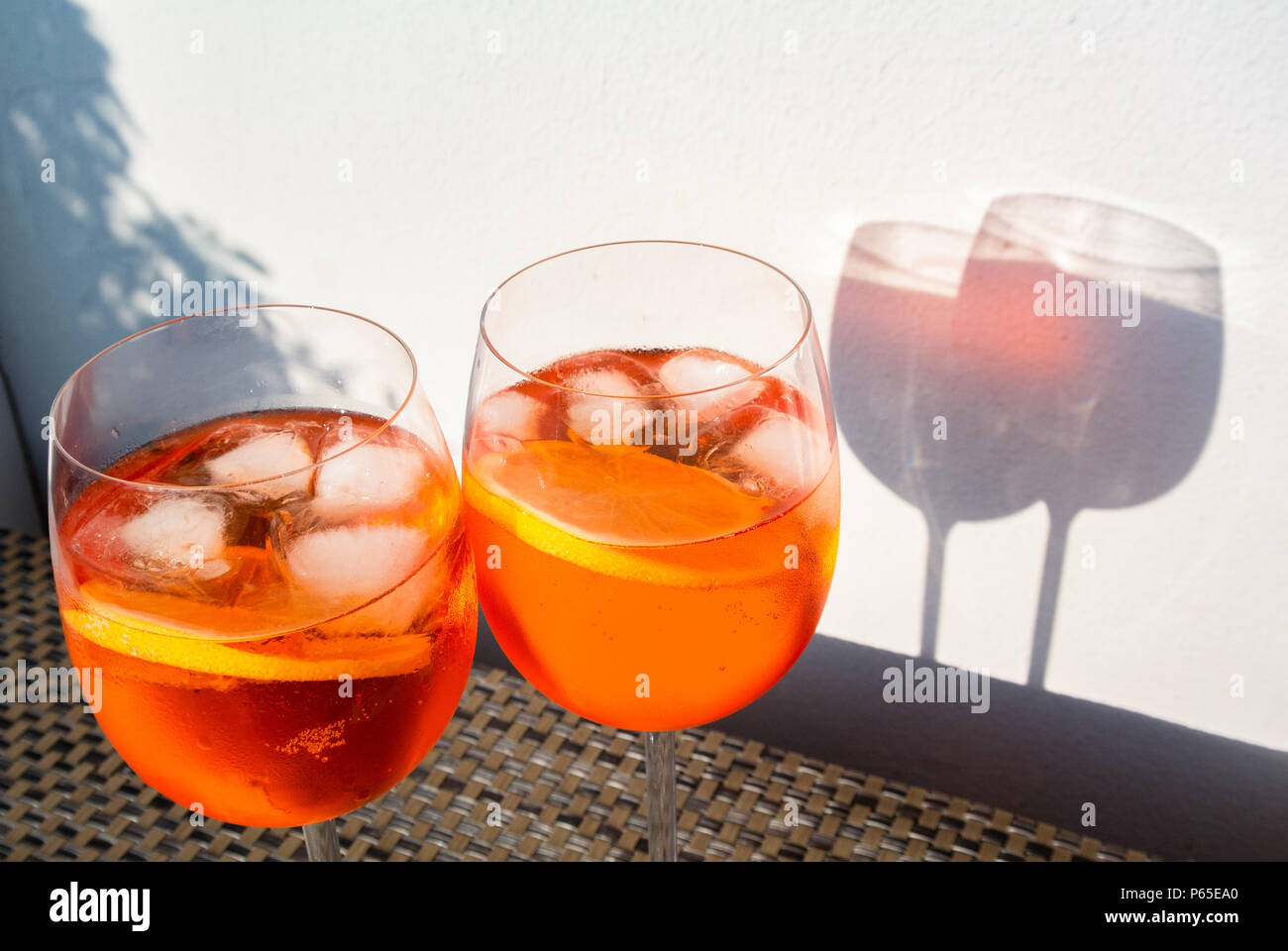 Aperol spritz with white background under sun shine - Stock Image