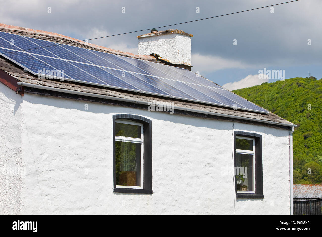 A 3 kilowatt solar voltaic panel array on an old house in Blawith, South Cumbria, UK. - Stock Image