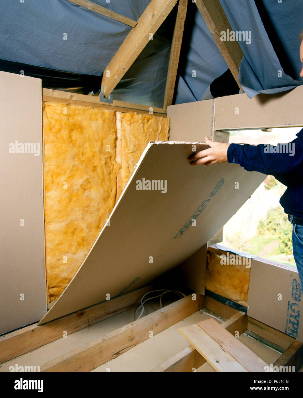 Insulating Installing Quilt Loft Insulation To A Roof Space Stock