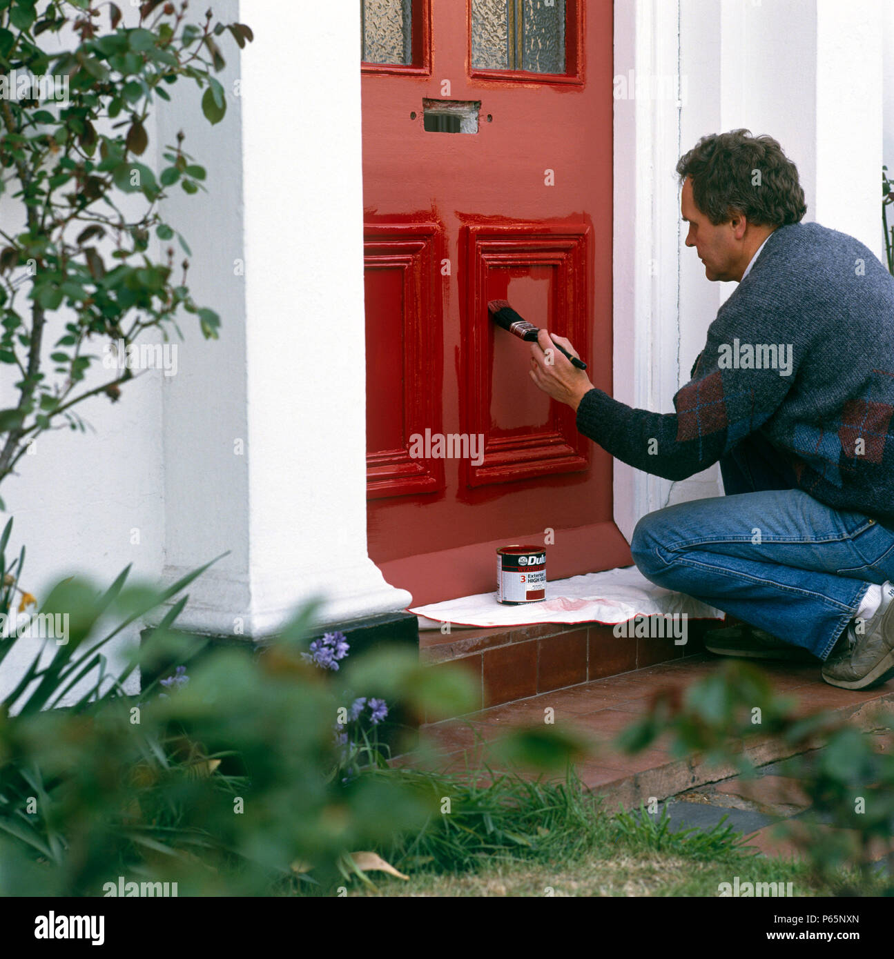 Painting A Front Door With Bright Red Paint Stock Photo 210339325
