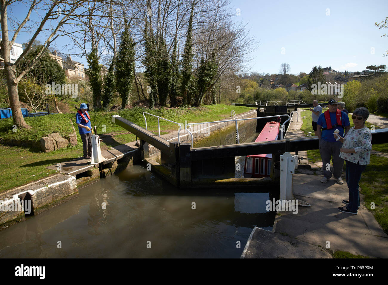 boaters working lock with narrowboat in number 12 lock as it floods with boat rising Kennet and Avon Canal Bath England UK - Stock Image
