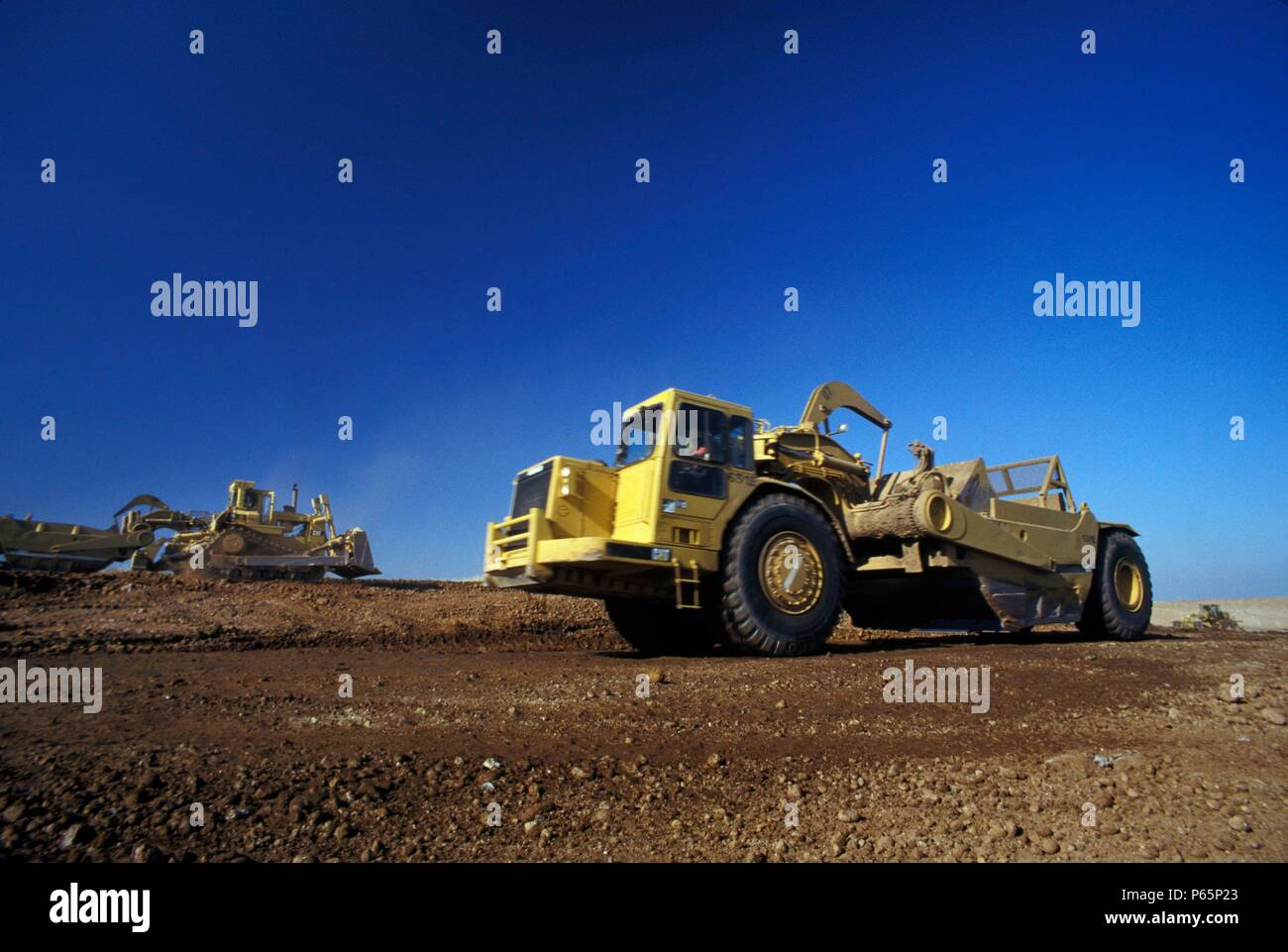 Scrapers and bulldozer working on road building for large California housing project, USA Stock Photo