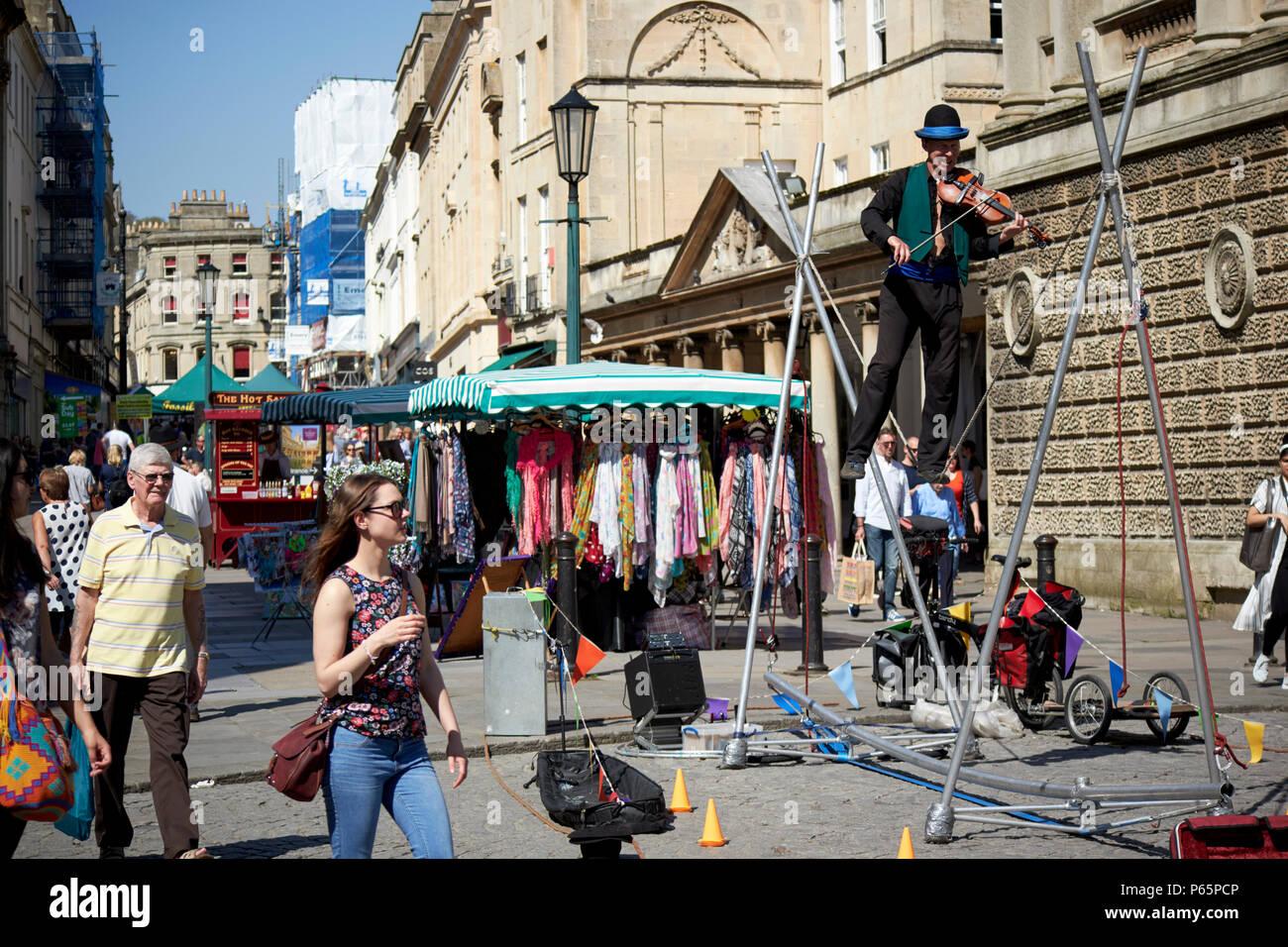 tightrope walker street entertainer on stall street Bath England UK - Stock Image