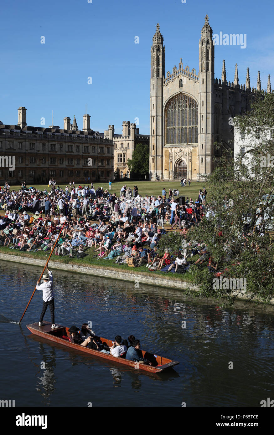 A Punt makes it's way along the river in front of Kings College Chapel at the University of Cambridge. - Stock Image