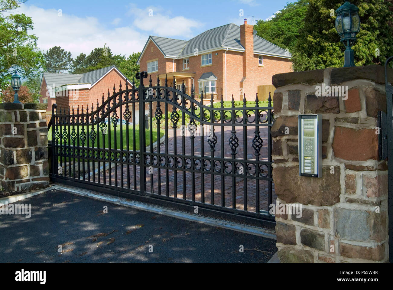 Security entrance electrically operated gate with inercom on new and prestigious housing development on Keckwick Hill, Daresbury near Warrington Chesh - Stock Image