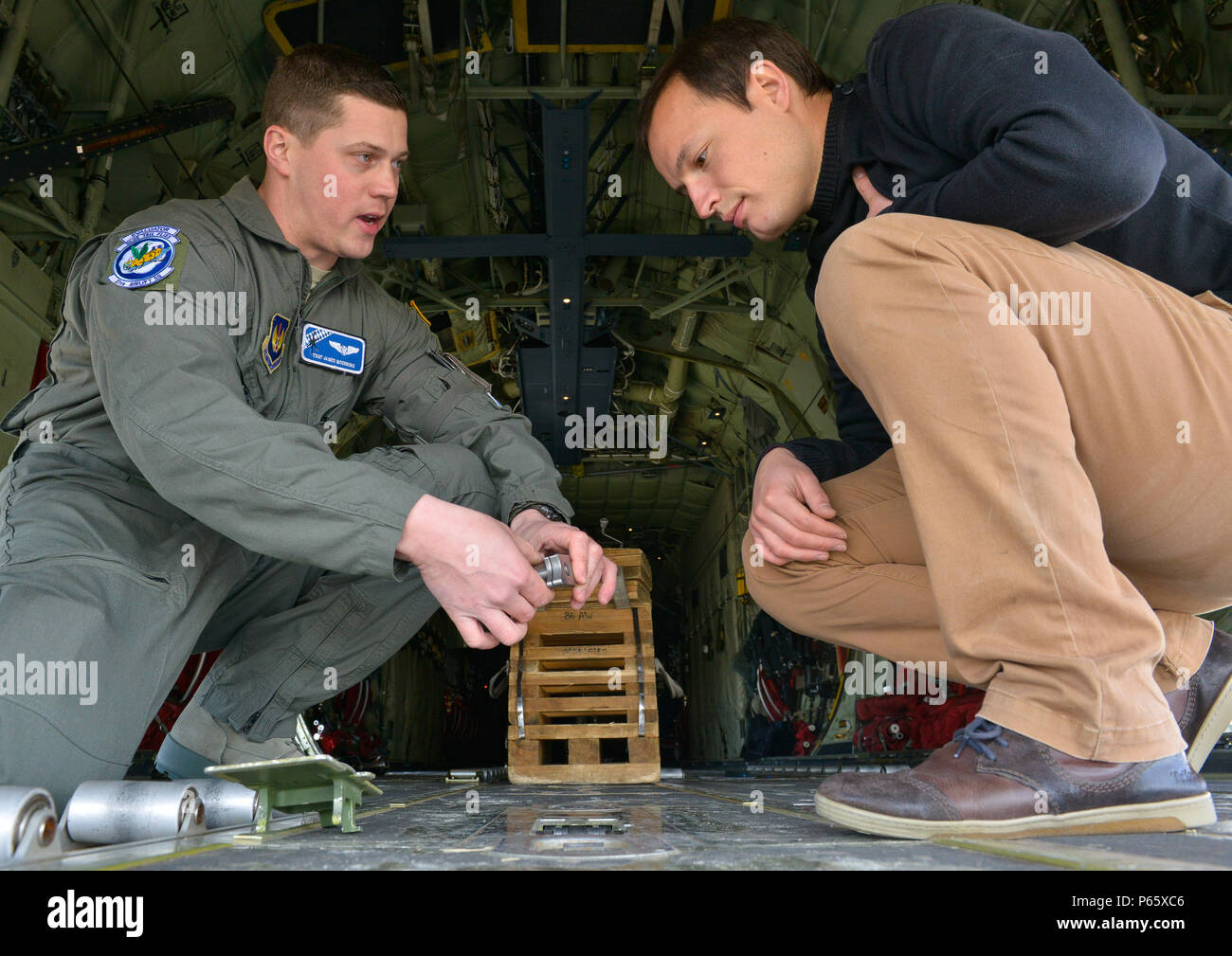 Tech. Sgt. James Moenning, 37th Airlift Squadron evaluator loadmaster and Pierre Yves, a French military contractor, evaluate a C-130J Super Hercules April 28, 2016, at Ramstein Air Base, Germany. Representatives from the French air force visited Ramstein Air Base to survey a C-130J Super Hercules and familiarize themselves with the aircraft and its capabilities. (U.S. Air Force Photo/ Airman 1st Class Lane Plummer) - Stock Image