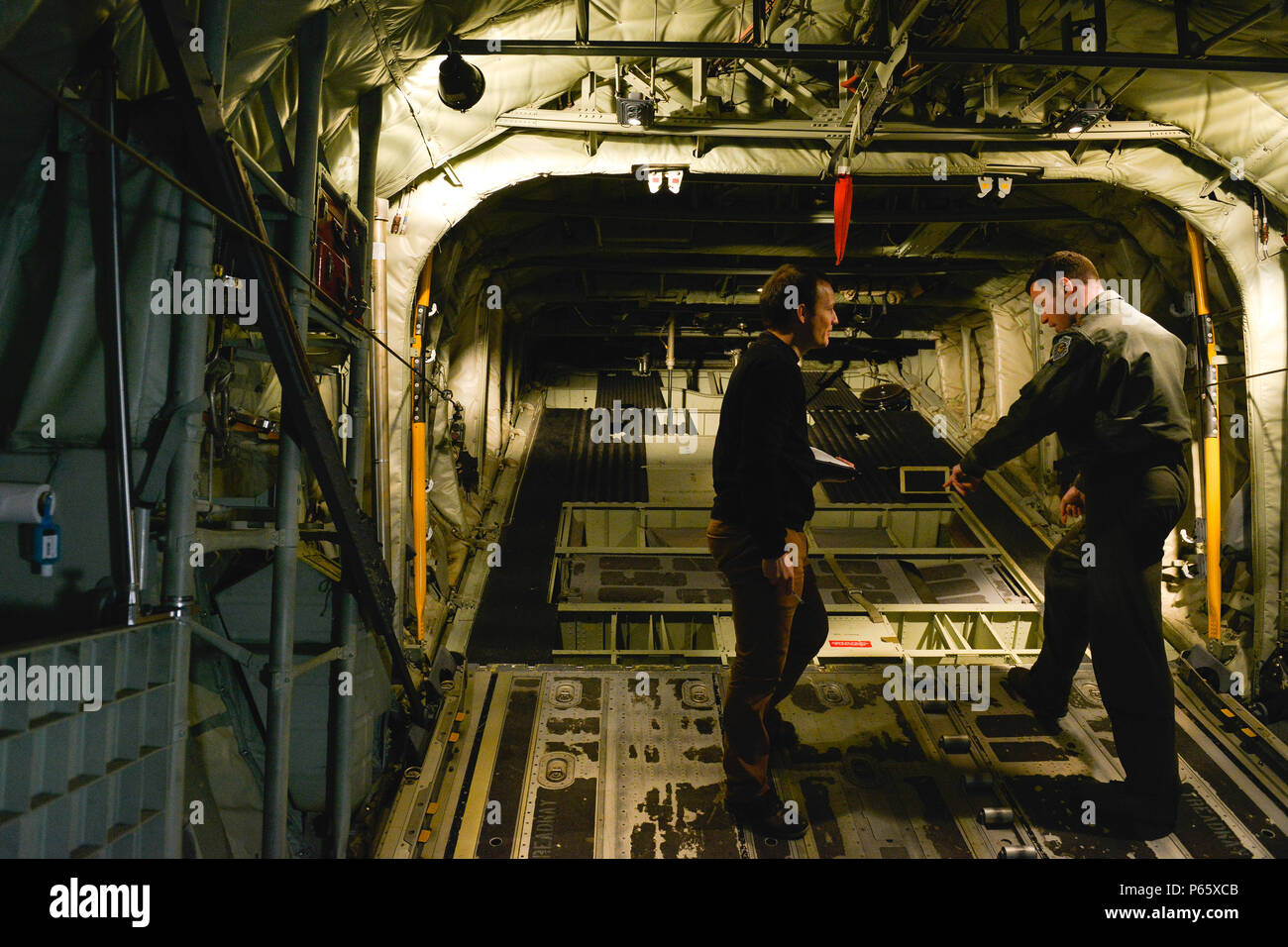 Tech. Sgt. James Moenning, 37th Airlift Squadron evaluator loadmaster, discusses the operations of a C-130J Super Hercules ramp with Pierre Yves, a French military contractor April 28, 2016, at Ramstein Air Base, Germany. The French air force recently purchased several C-130s and visited the 37th Airlift Squadron to survey the aircraft in order to better understand its features and capabilities. U.S. Air Force Photo/ Airman 1st Class Lane Plummer) - Stock Image