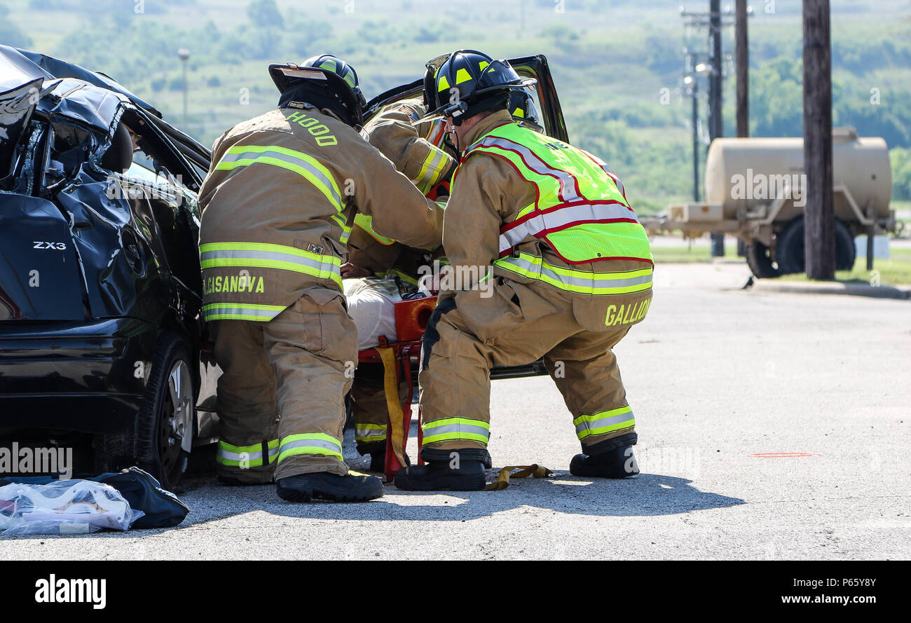 Three members of the Fort Hood Fire Department, actively attempt to remove a simulated car crash victim during the annual Fort Protection Exercise at Fort Hood, Texas, May 11. The passenger received facial lacerations and possible back injuries from the collision. (U.S. Army photo by Staff Sgt. Gene Arnold, 14th Public Affairs Detachment) (Released) - Stock Image