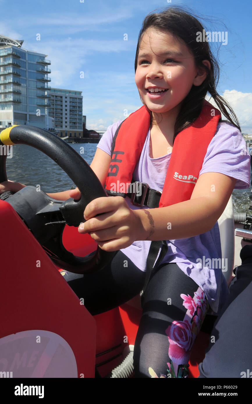 Young girl having fun steering a boat in Cardiff - Stock Image