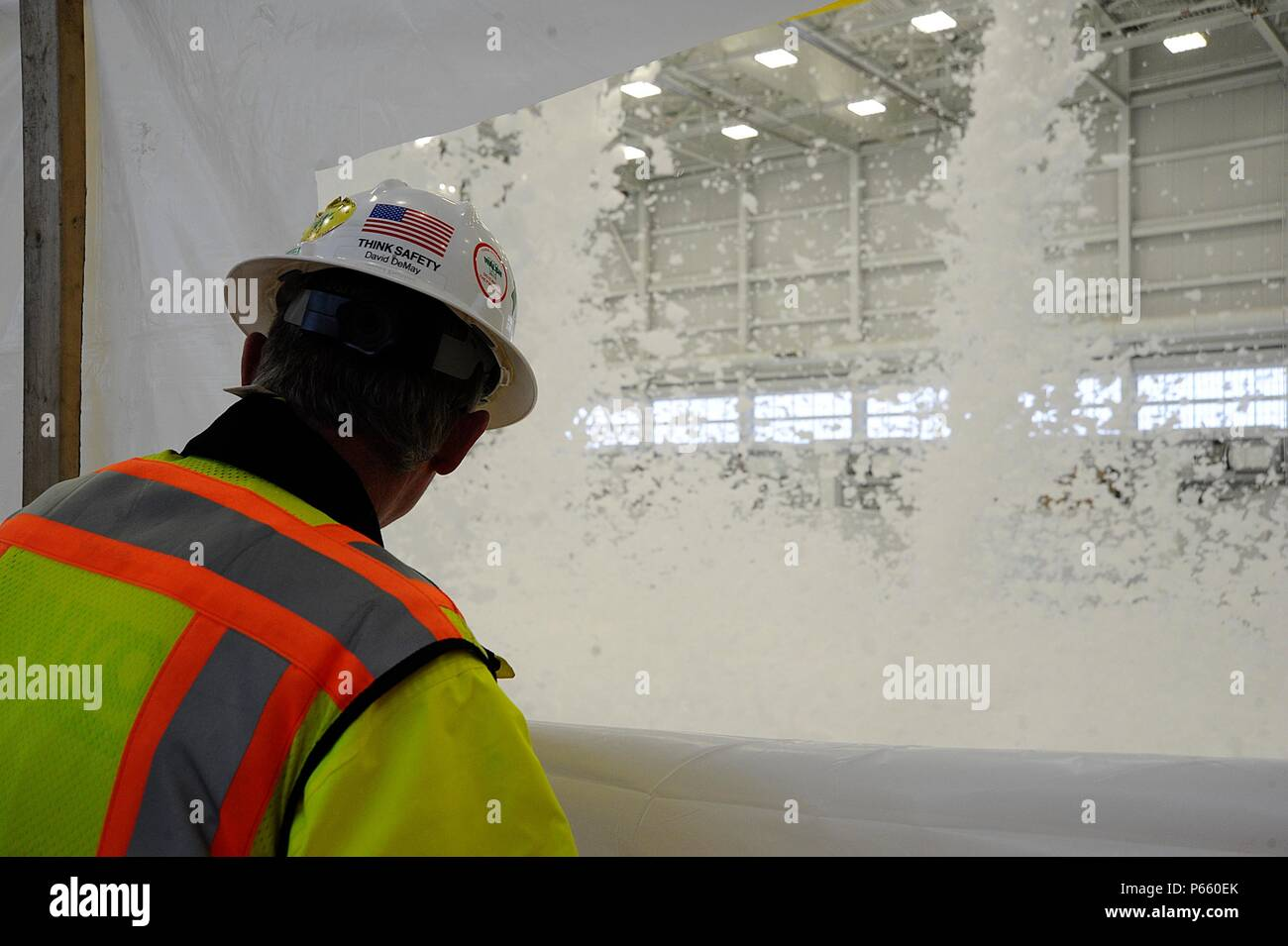 David Demay, construction site manager, watches foam rain down in a hangar during a fire suppression safety test, May 3, 2016, at McConnell Air Force Base, Kan. The new hangars will house the KC-46's, which are scheduled to arrive here in Spring 2017. The foam is dispensed from generators in the top of the hangar which expand and suffocate fire. (U.S. Air Force photo/Airman 1st Class Jenna K. Caldwell) Stock Photo