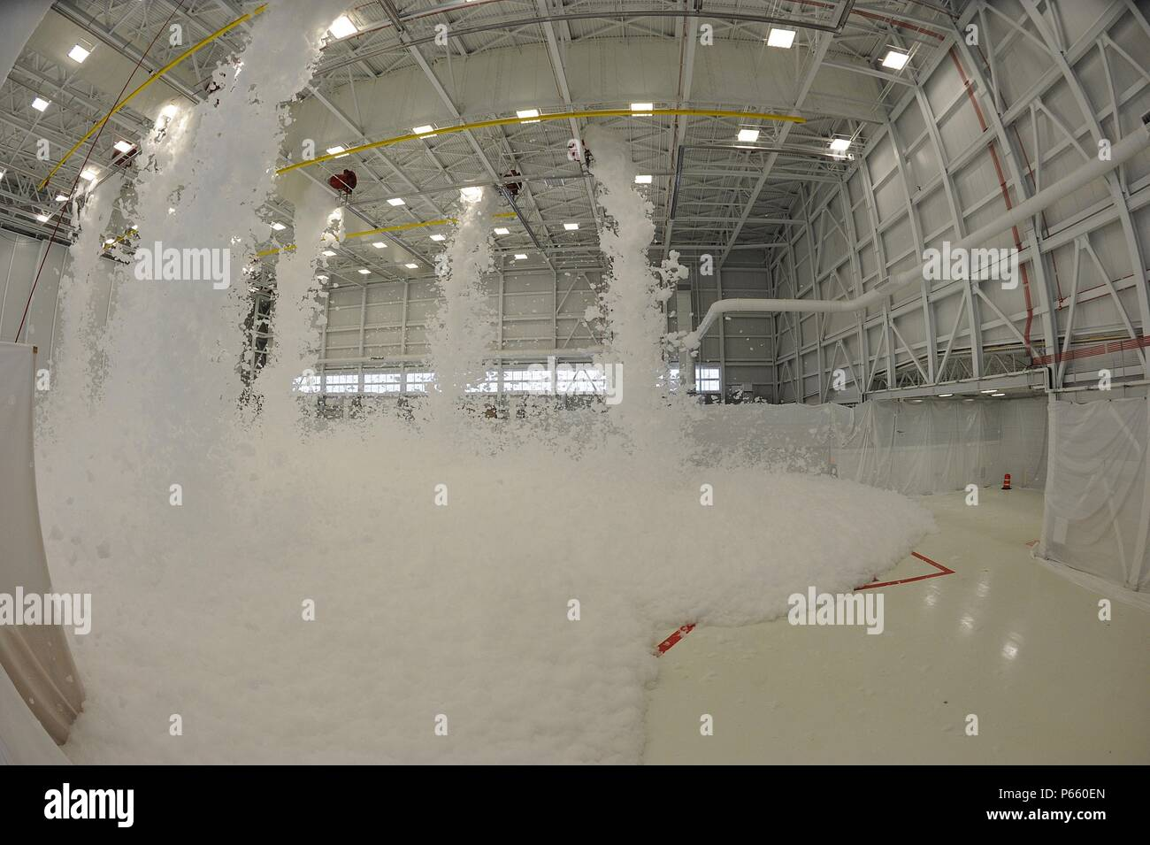 Foam rains down in a hangar during a fire suppression safety test, May 3, 2016, at McConnell Air Force Base, Kan. The new hangars will house the KC-46's, which are scheduled to arrive here in Spring 2017. As a safety feature, foam is dispensed from generators in the top of the hangar which expand and suffocate fire. (U.S. Air Force photo/Airman 1st Class Jenna K. Caldwell) Stock Photo