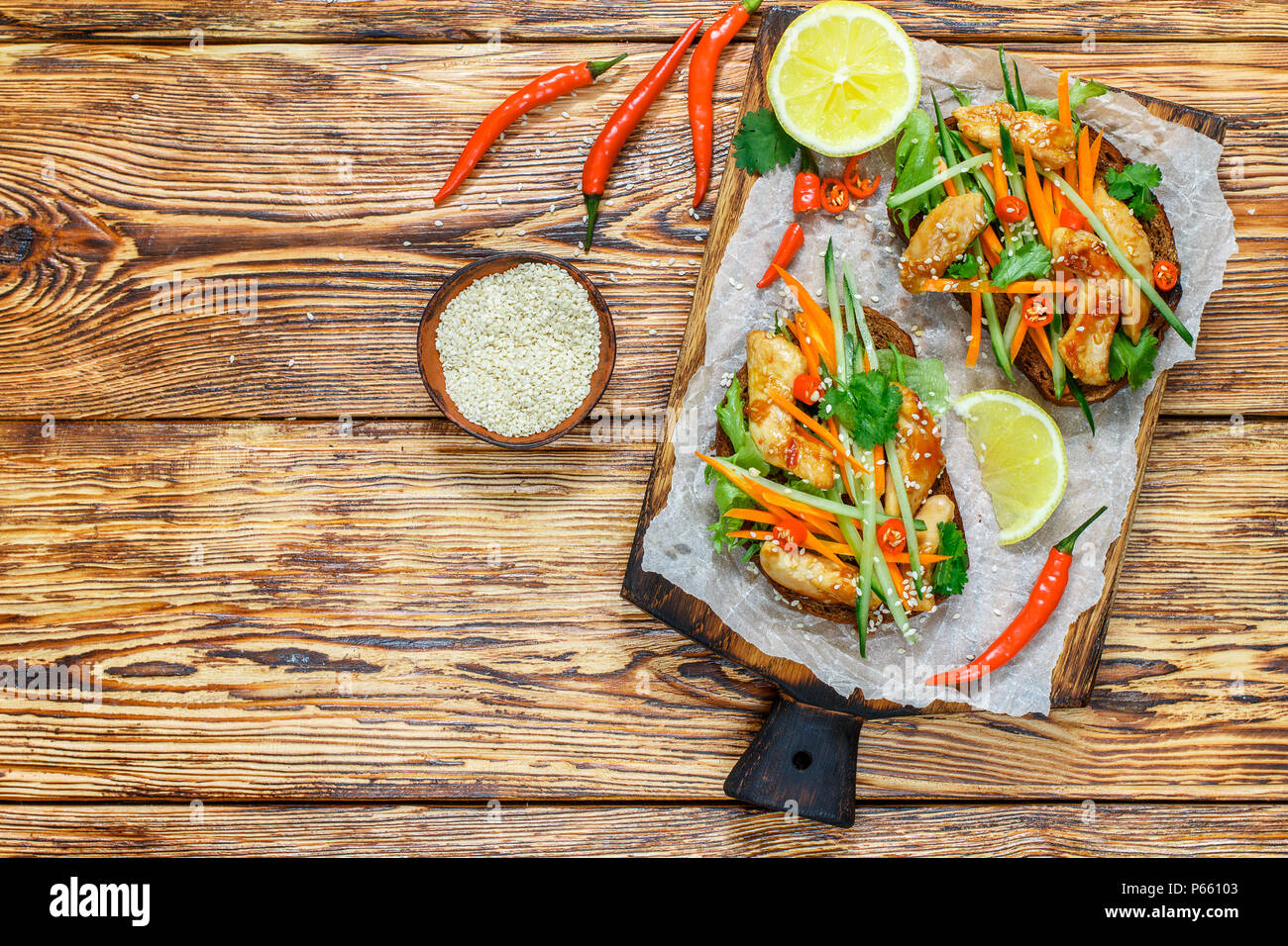 Asian sandwich with fried chicken and fresh vegetables-carrots, cucumber, chili pepper, cilantro and sesame. Selective focus. Top view and copy space - Stock Image