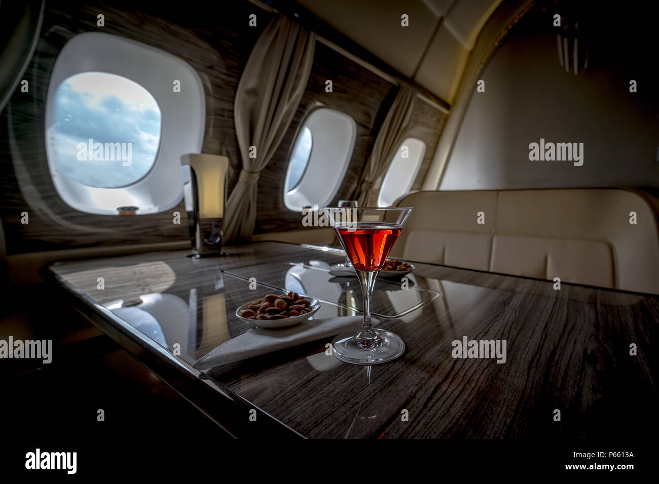 Interior of a business class of a commercial passenger plane, an armchair and a window, a table and a cocktail glass with a drink and almonds. - Stock Image