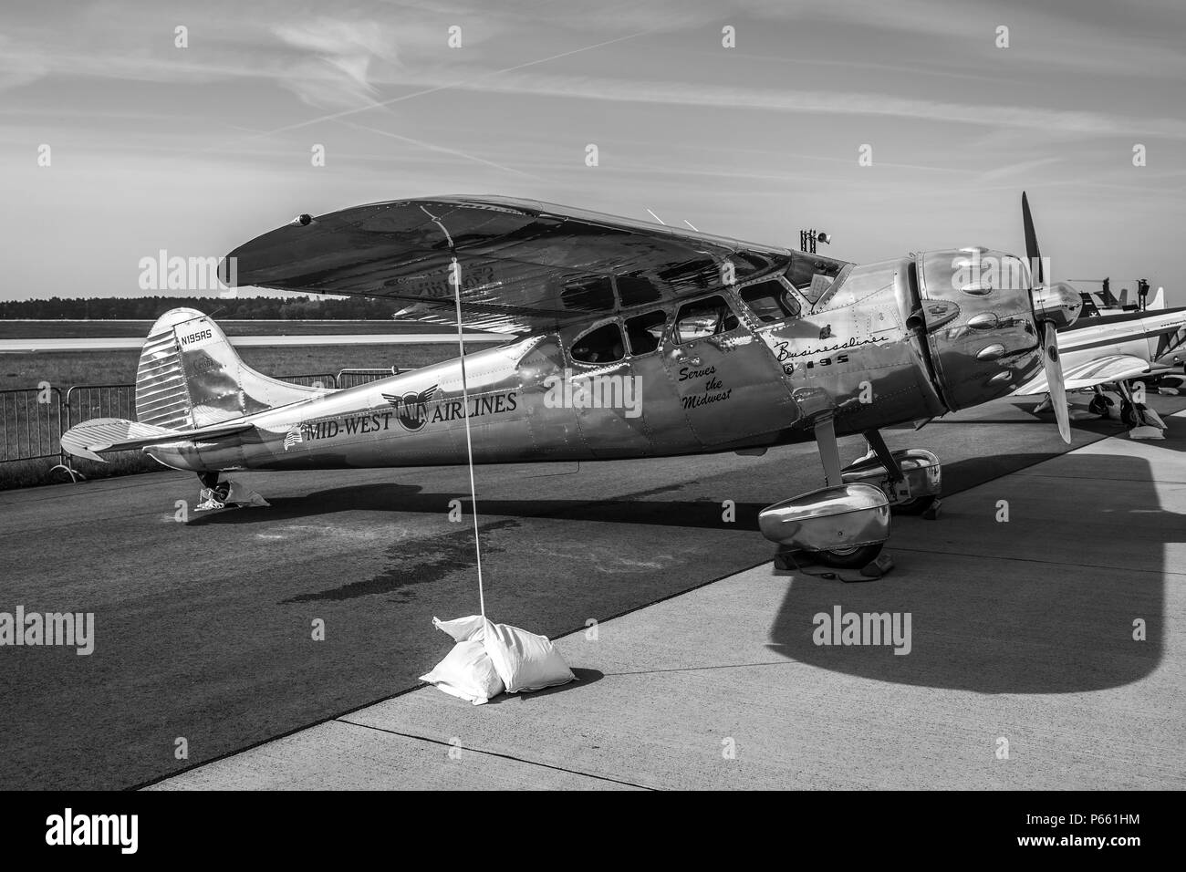 BERLIN - APRIL 27, 2018: Light personal and business aircraft Cessna 195A by Mid-West Airlines on the airfield. Black and white. Exhibition ILA Berlin - Stock Image