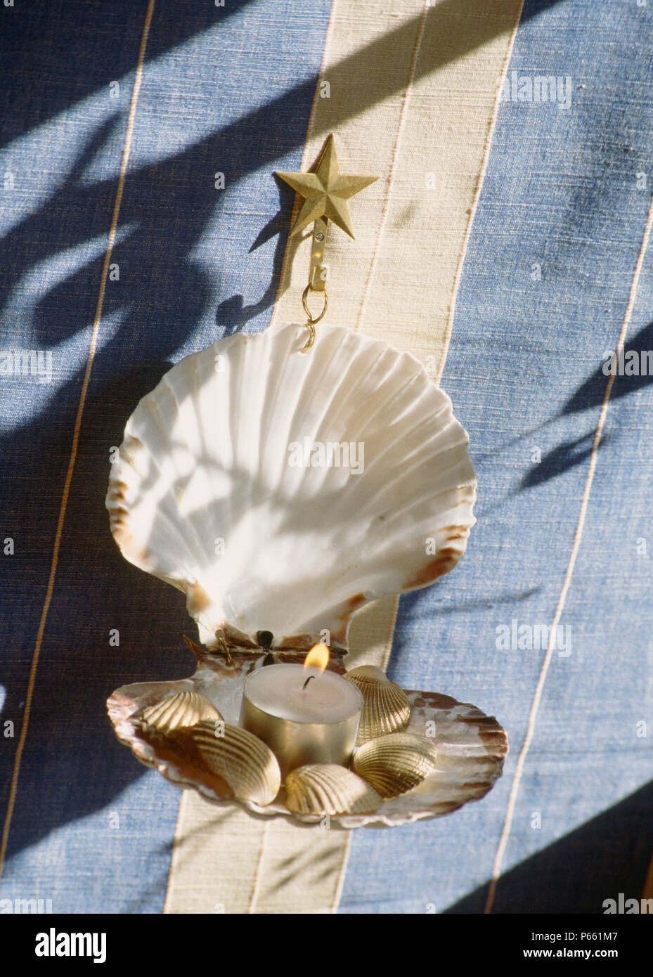 Close Up Of Hand Made Seashell Wall Sconce With Lighted Candle Stock