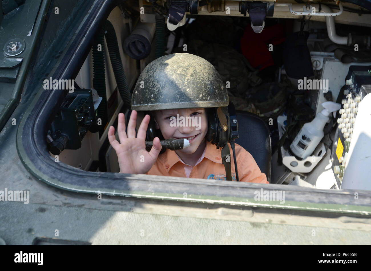 A young Moldovan boy smiles and waves as he sits inside a U.S. Army M1132 Engineer Squad Vehicle (ESV), Stryker, during a static display in Chisinau, Moldova, May 8, 2016. (Photo by U.S. Army Staff Sgt. Steven M. Colvin) - Stock Image