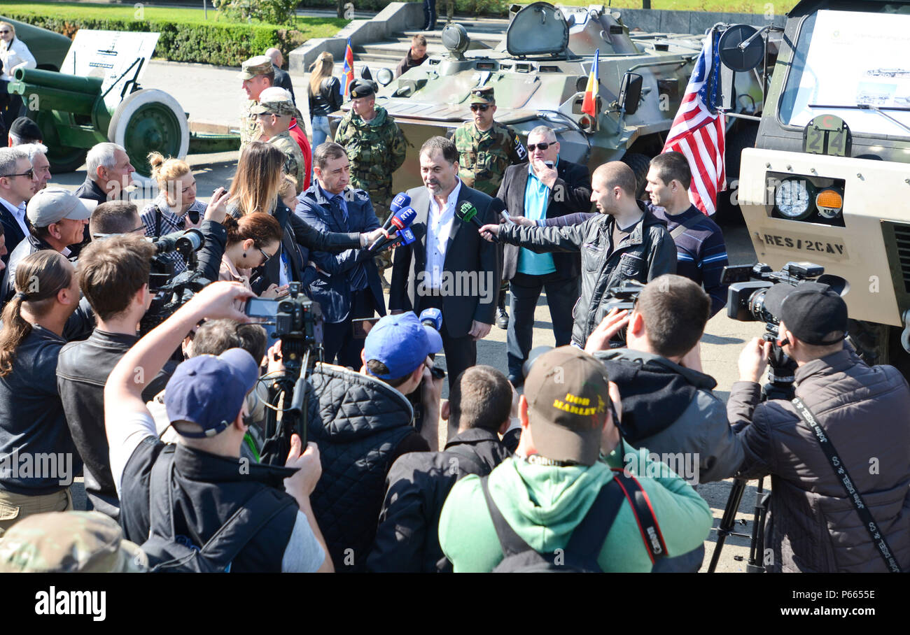 Several media outlets surround the Minister of Defense of Moldova, Anatol Salaru, to ask him some questions regarding America's presence in Moldoava during a static display in Chisinau, Moldova, May 5, 2016. (Photo by U.S. Army Staff Sgt. Steven M. Colvin/Released) - Stock Image
