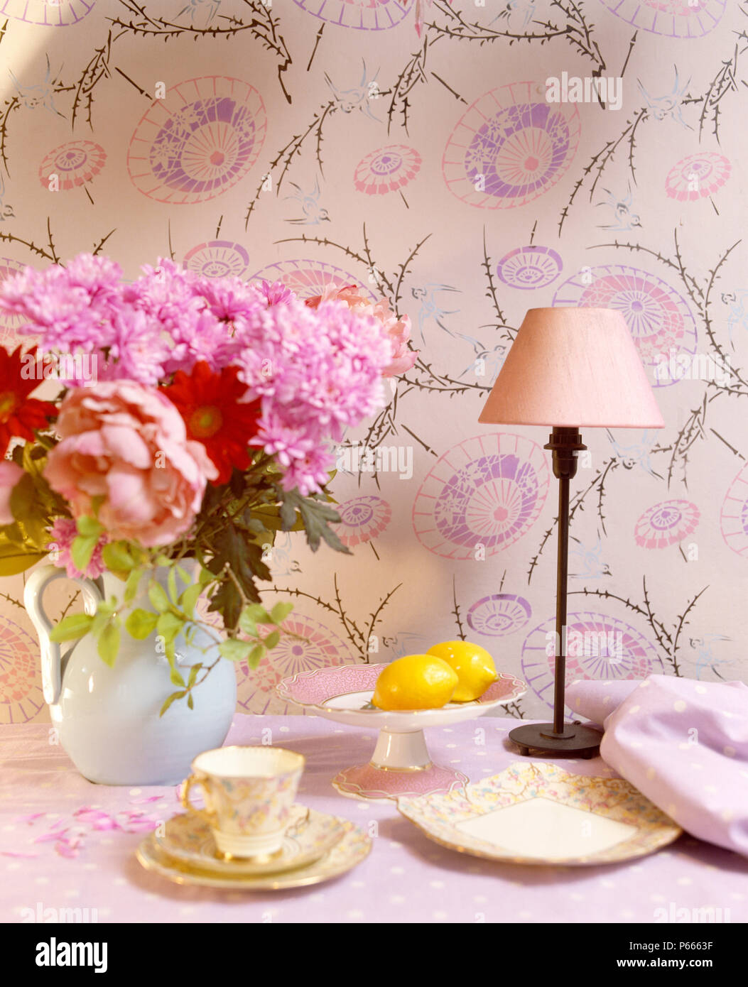Still Life Of Jug Of Pink Summer Flowers On Table With Lamp And
