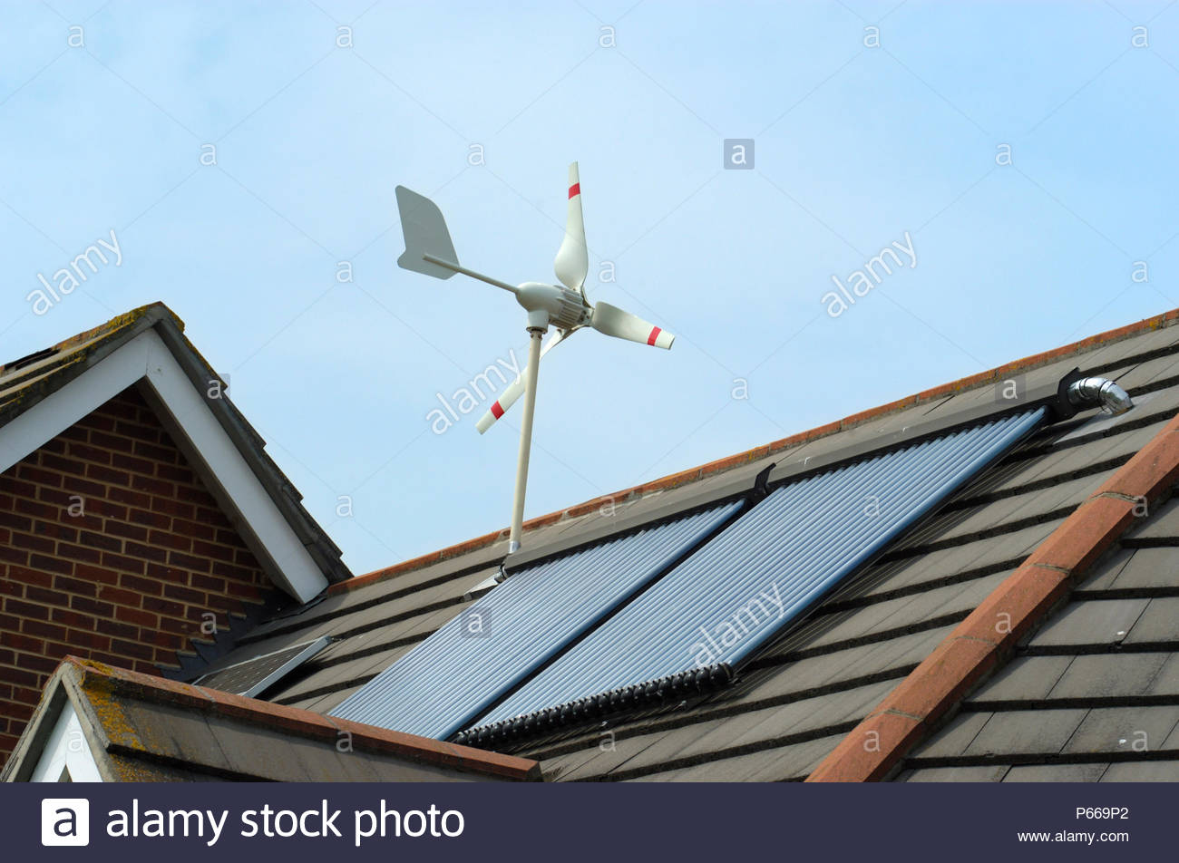 Micro Wind Turbine, Solar Voltaic and Evacuated solar tubes on roof of house in Ferndown Dorset England. - Stock Image