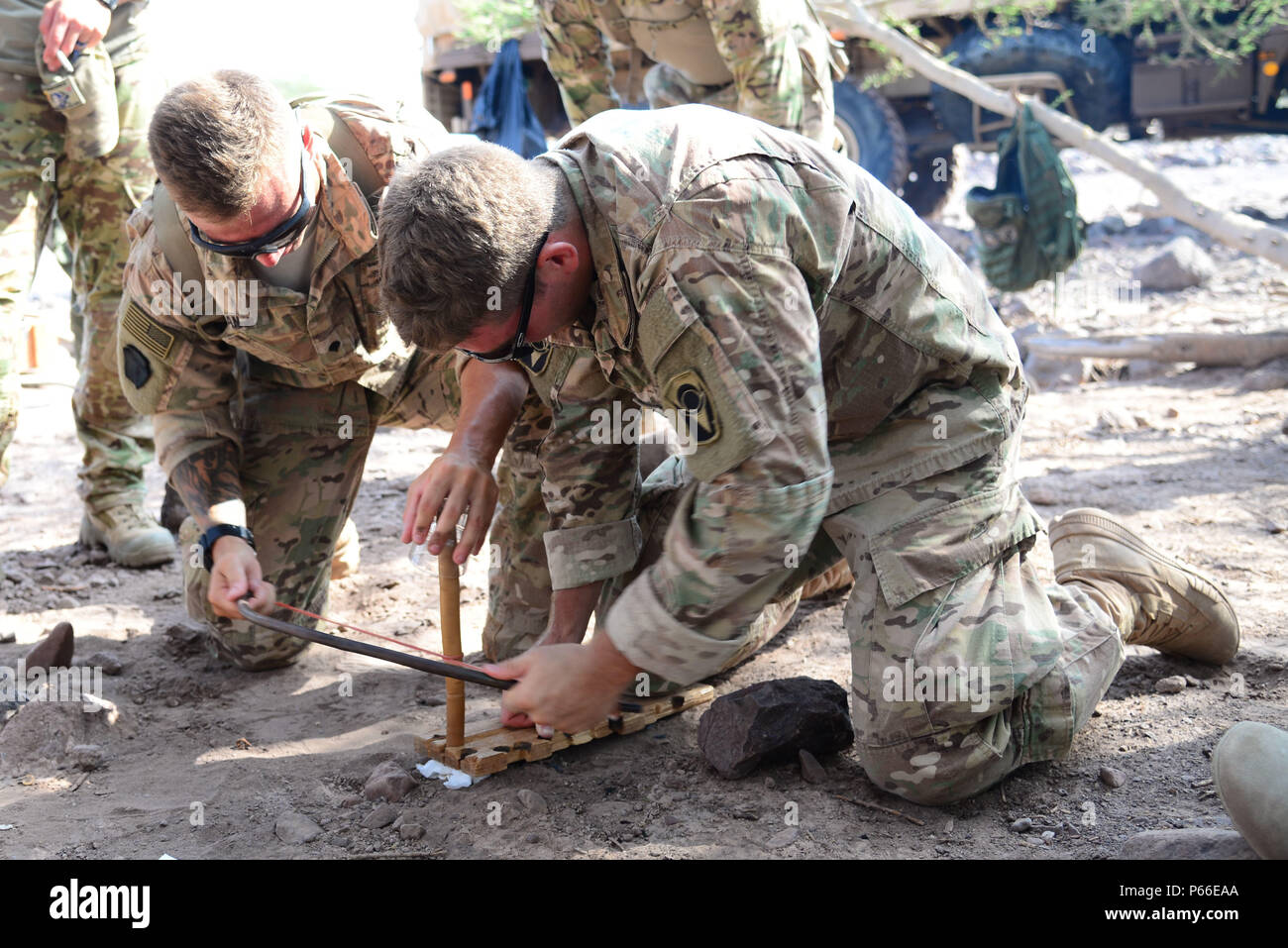 U.S. Army Spc. Zach Dean, left, and Jacob Currie, 2nd Battalion, 124th Infantry Regiment, use a stick, bow and paper to make a fire during the French Desert Survival Course, May 5, 2016 at Arta Plage, Djibouti. During the course, U.S. forces also learned how to make fire from mundane items like batteries, flint, bullets and steel wool. (U.S. Air Force photo by Senior Airman Benjamin Raughton/Released) - Stock Image
