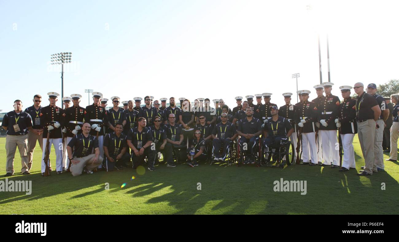 Members of the U.S Marine Corps Silent Drill Platoon pose with U.S. Marines, Sailors, and staff with the Wounded Warrior Regiment before the opening ceremony of the 2016 Invictus Games at the ESPN Wide World of Sports in Oralndo, Fla., May 8, 2016. The Invictus Games is an international adaptive sports competition for wounded, ill, and injured Service members and veterans. (U.S. Marine Corps Photo by Capt. Andrew Bolla/Released) Stock Photo