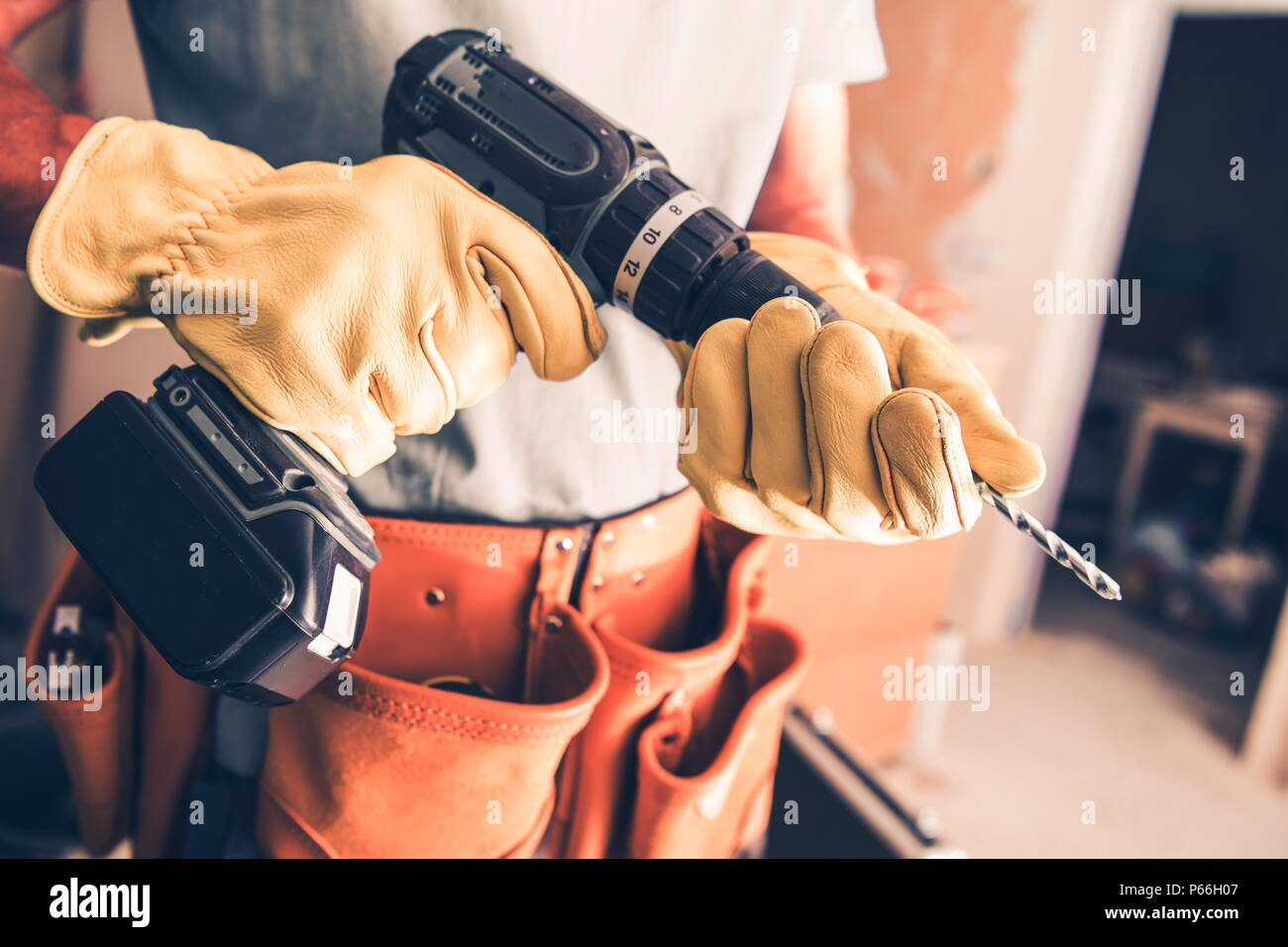 Contractor Worker with Power Tool Preparing For Drywall Installation. - Stock Image