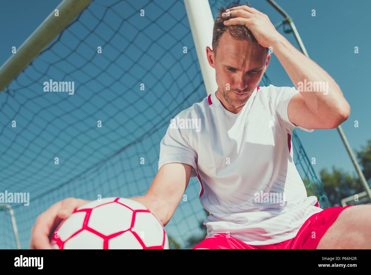 Heartbroken Caucasian Football Player in His 30s with the Ball on the Soccer Field. - Stock Image
