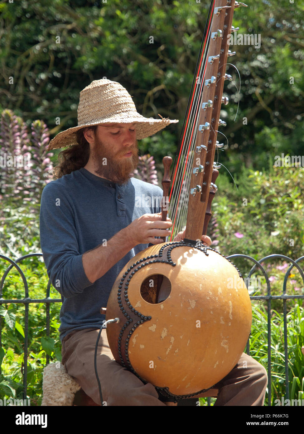 Busking in Pavilion Gardens, Brighton a man plays an African harp - Stock Image