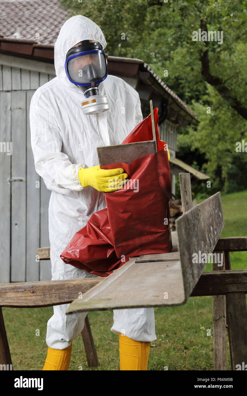 A Worker with mask packing Asbestos Disposal - Stock Image