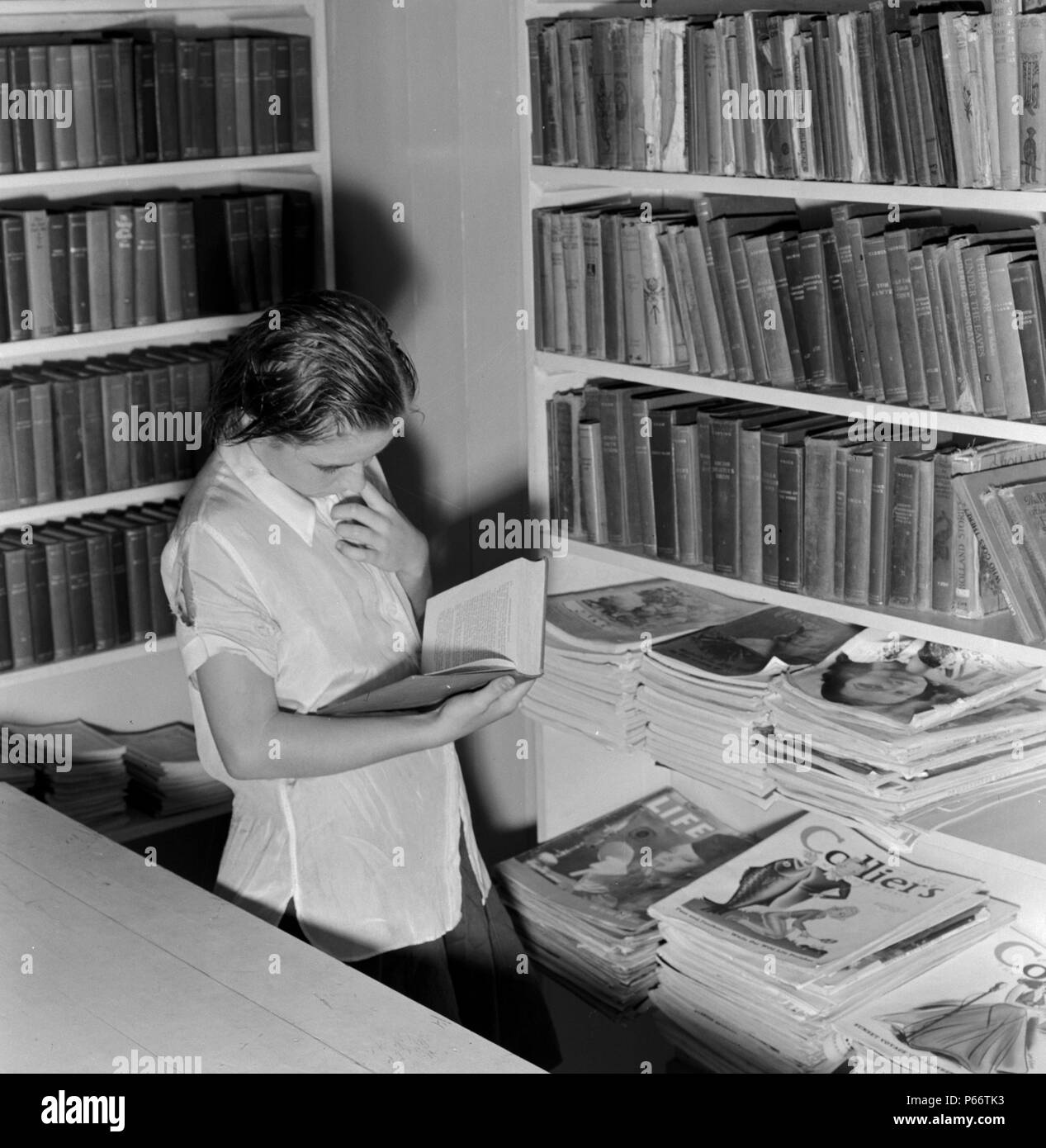 Arvin camp for migrant workers (Farm Security Administration-FSA) California. A small library in camp with Works Progress Administration (WPA) librarian in charge is now available to agricultural workers. Part of the program for recreational and education instituted in all government camps for migratory farm families 1938 - Stock Image