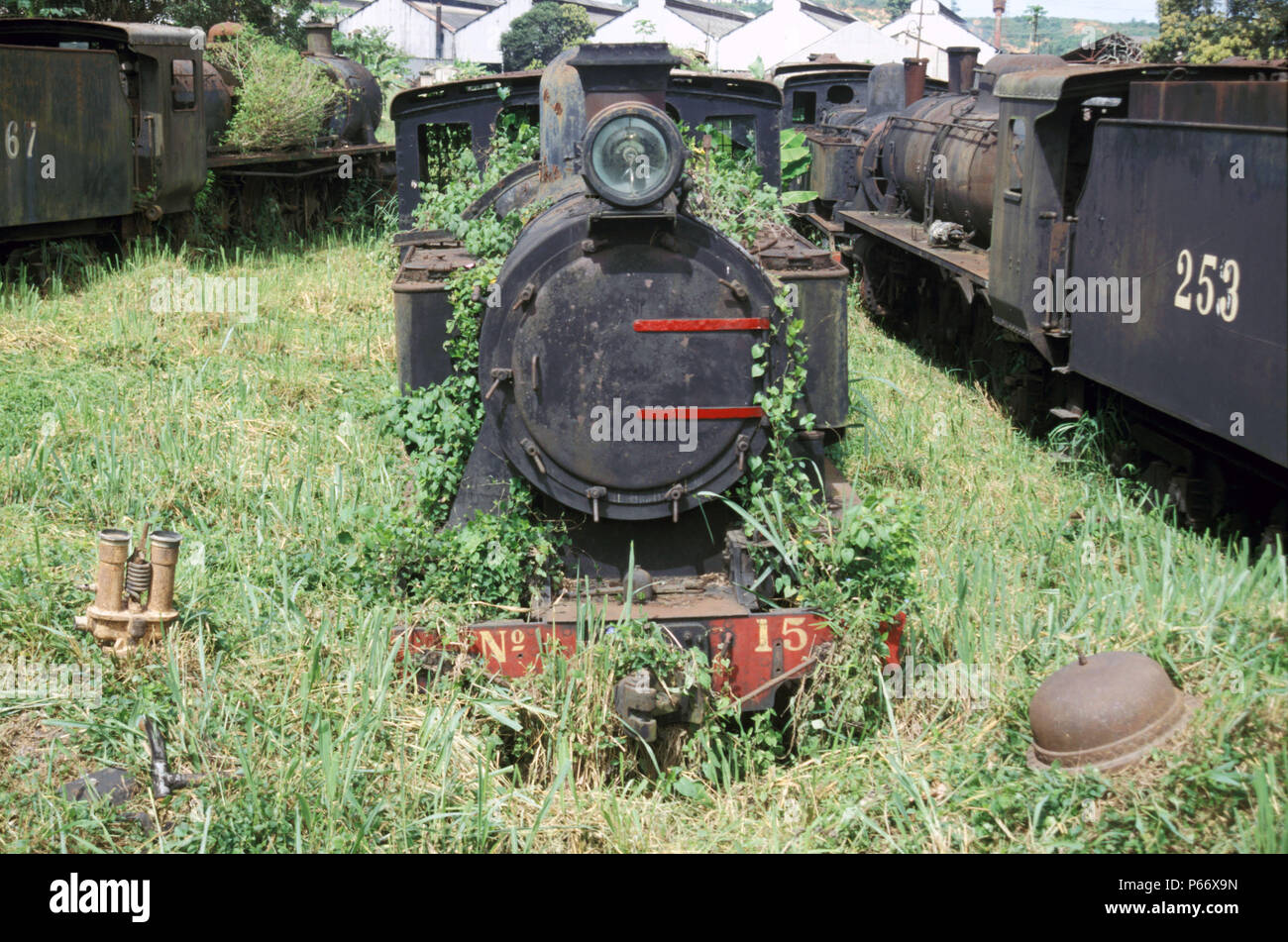 Abandoned British built locomotives at Location Works Ghana in 1985, The main works buildings can be seen in the far background. - Stock Image