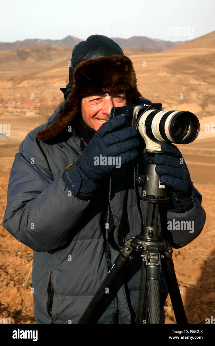 Colin Garratt on location near Xiakengzi on the fabled Jing Peng pass in Inner Mongolia, March 2004. - Stock Image