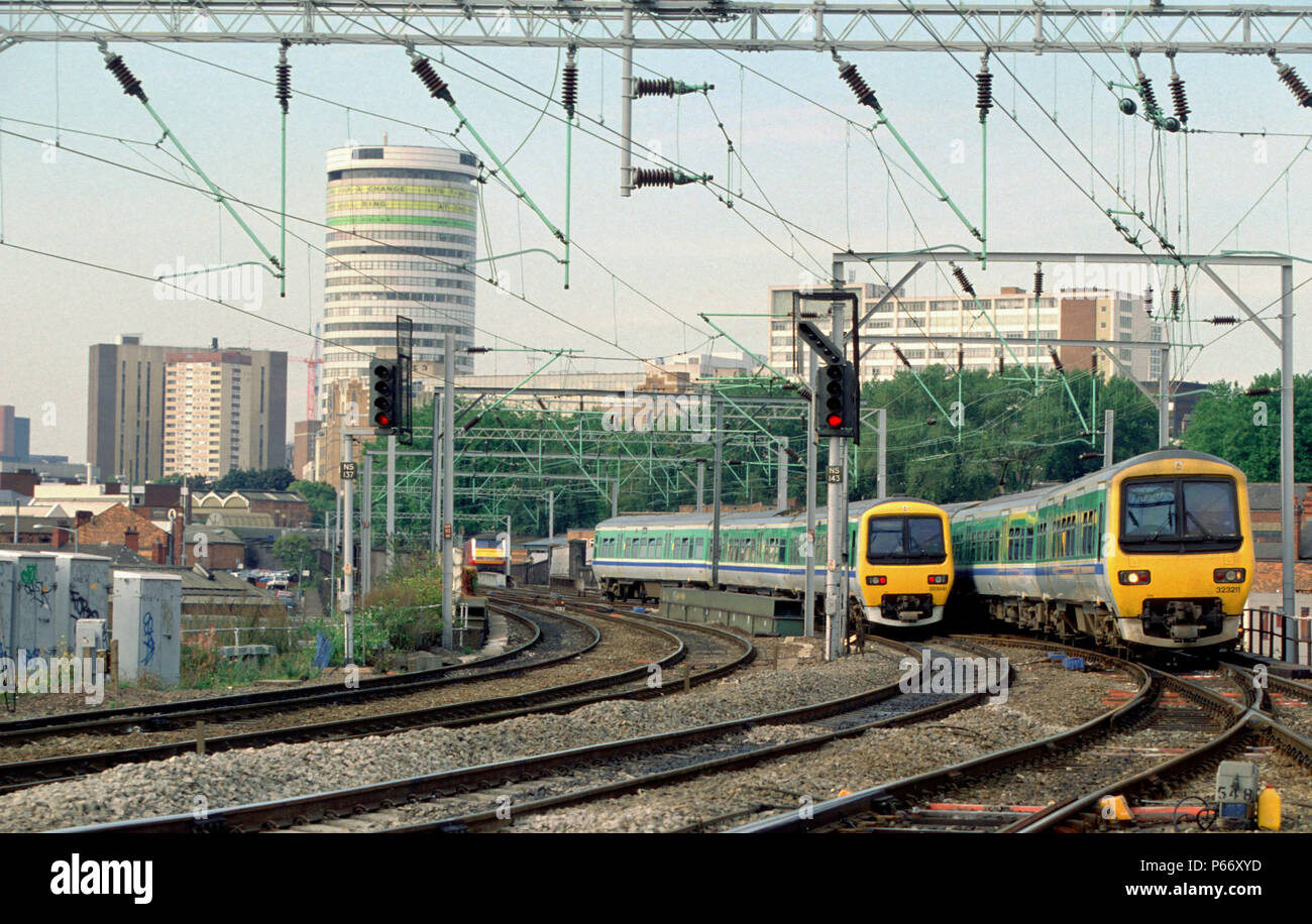 Dominated by Birmingham's landmark Rotunda a pair of Centro local services, worked by EMU sets, cross at Proof House Junction just outside Birmingham  - Stock Image