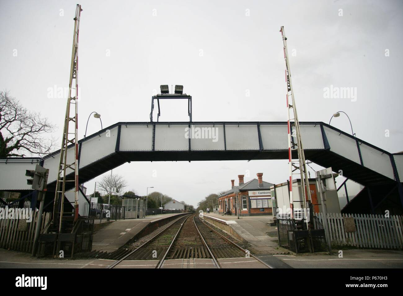 The level crossing and footbridge at Cambourne station, Cornwall, with the station building and platforms beyond. 2006 - Stock Image