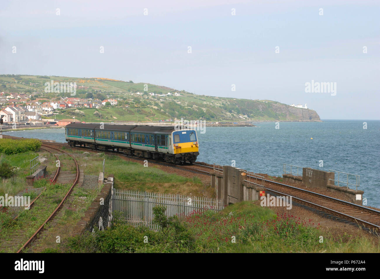 A service from Larne to Belfast skirts the coast at Whitemoor in County Antrim - Stock Image