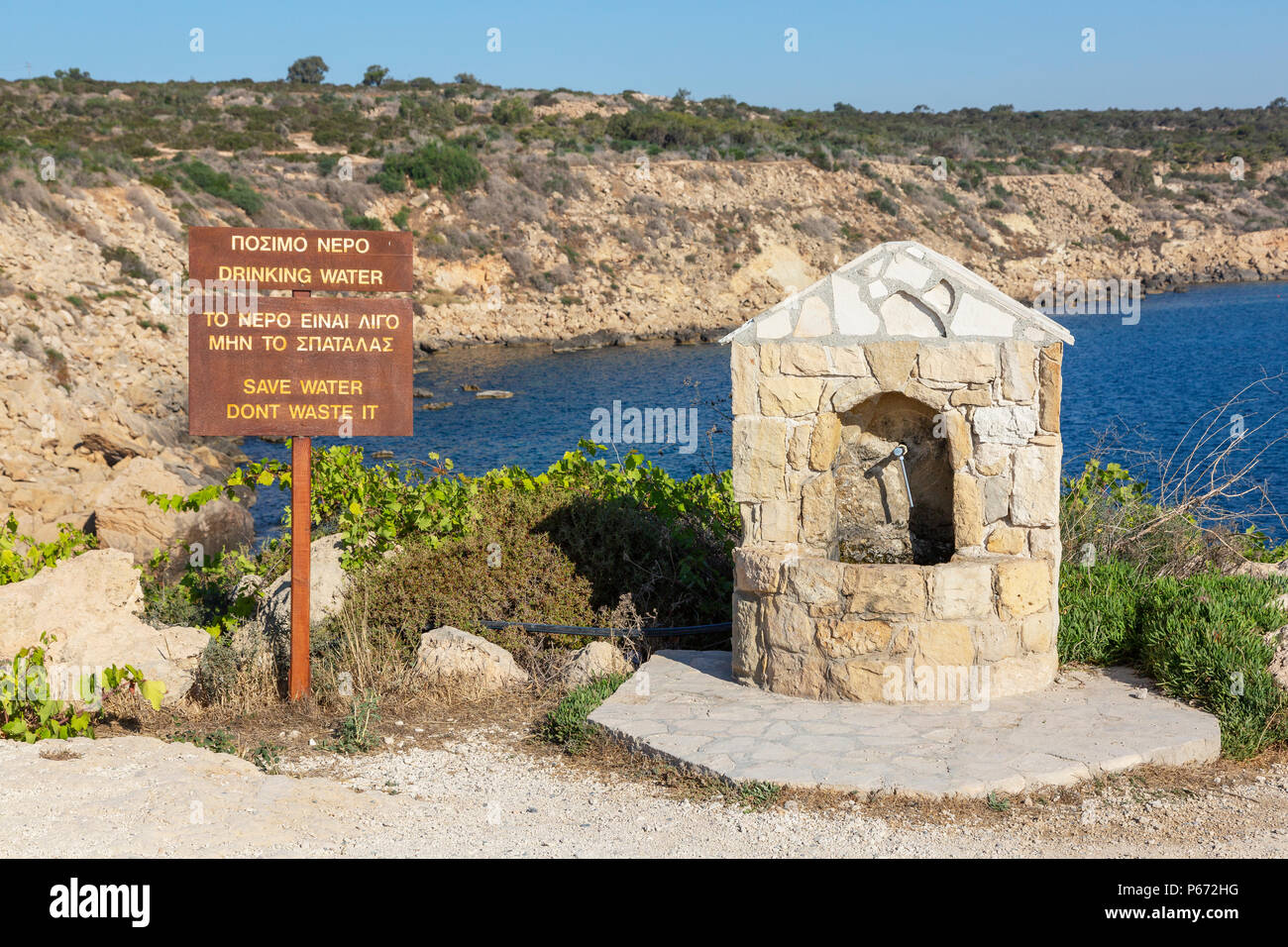 Public water drinking fountain with a warning sign about not wasting water near Korakas Bridge, Cyprus - Stock Image