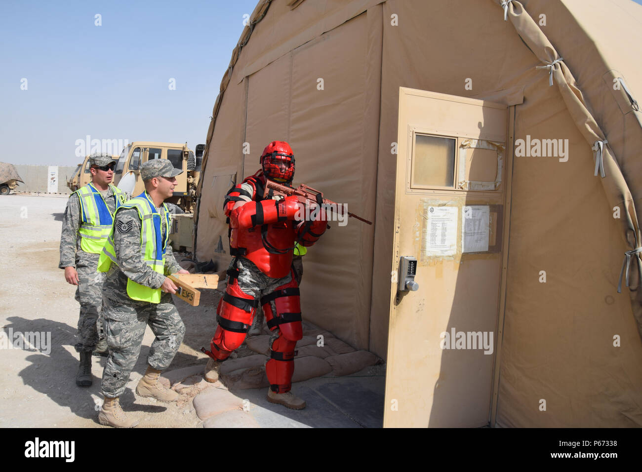 Tech. Sgt. Shawn Rankins, 379th Expeditionary Security Forces Squadron Check Six Team, begins an active shooter exercise with Army Soldiers May 5, 2016, at Al Udeid Air Base, Qatar. Staff Sgt. Joseph Brock, also from the 379th ESFS,  portrayed the shooter and wore a red padded suit to protect himself from Soldiers' physical retaliation as Tech. Sgt. Scott Carpenter, 379th ESFS, strikes two pieces of wood together to simulate gun shots. Check Six teaches Airmen to be aware of their surroundings at all times, and most importantly how to defend themselves and others in the event a hostile threat  - Stock Image