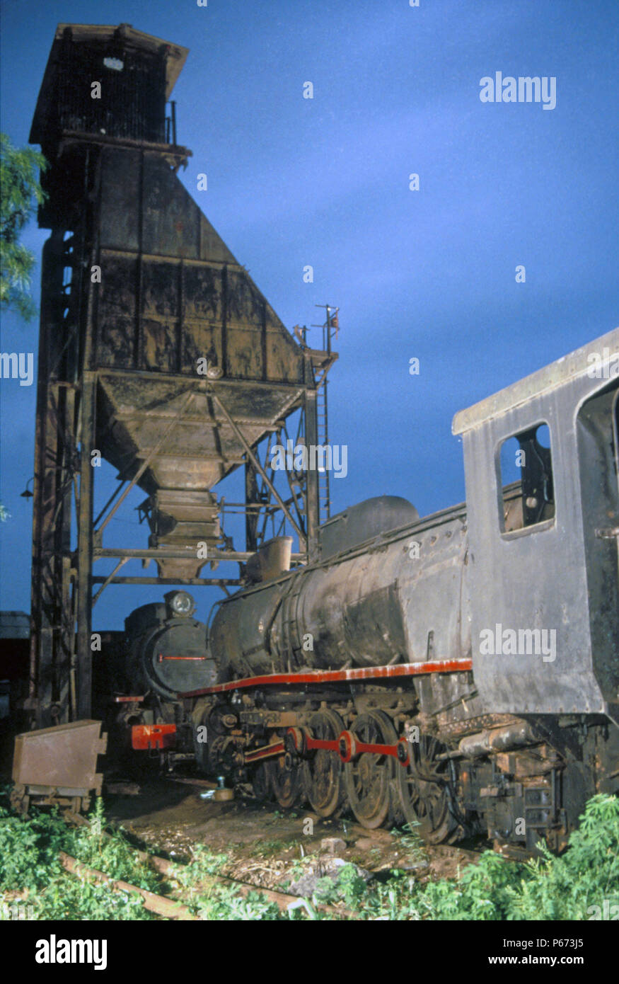 Abandoned Ghanaian locomotives beneath the coaling tower in Accra. Vulcan Foundry 4-8-2 No.266 'Techiman' with Giesl chimney in foreground with No.255 - Stock Image