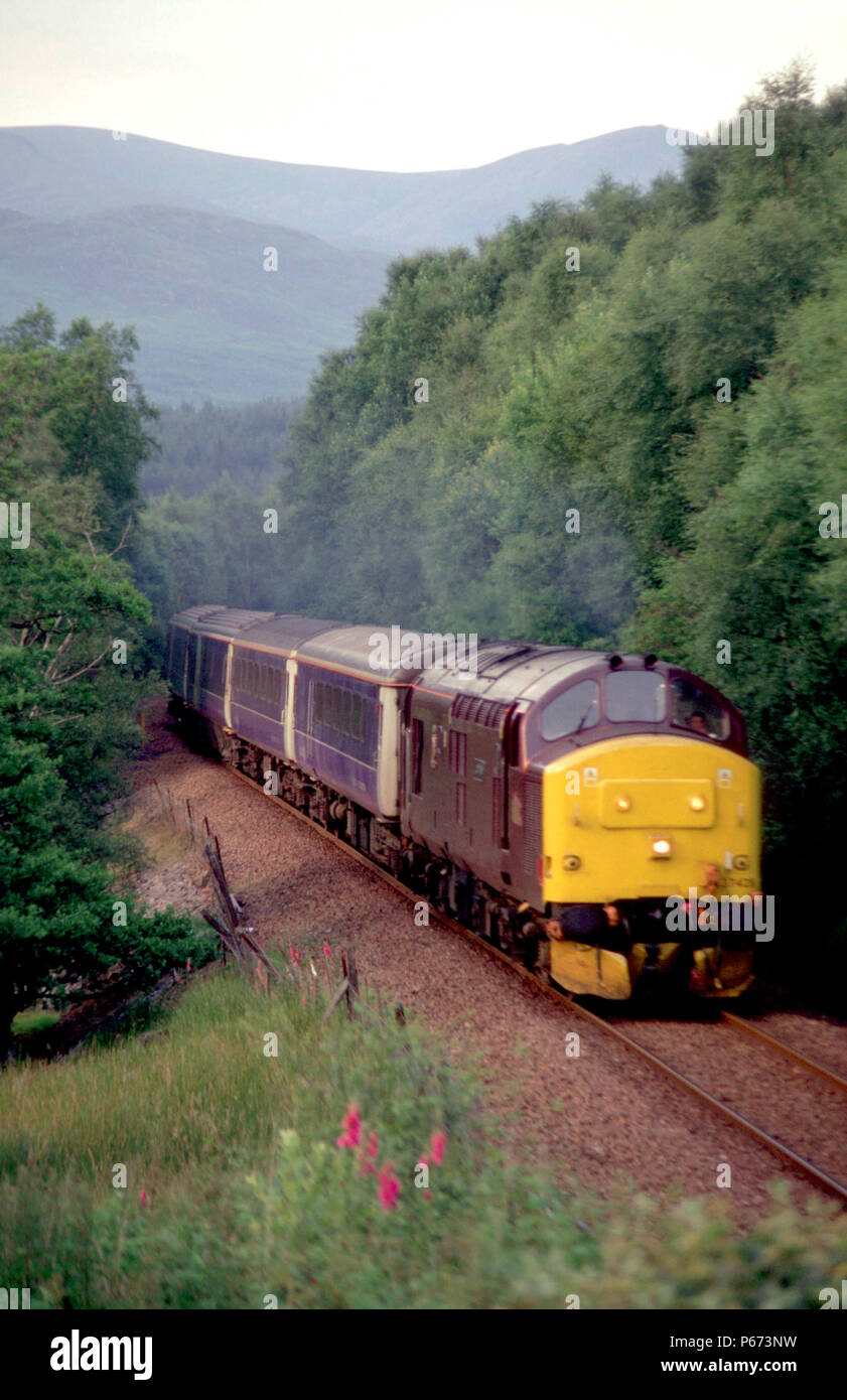 An EWS class 37 locomotive pulls a Scotrail Caledonian Sleeper service southbound shortly after leaving Tulloch station. This train started its journe - Stock Image