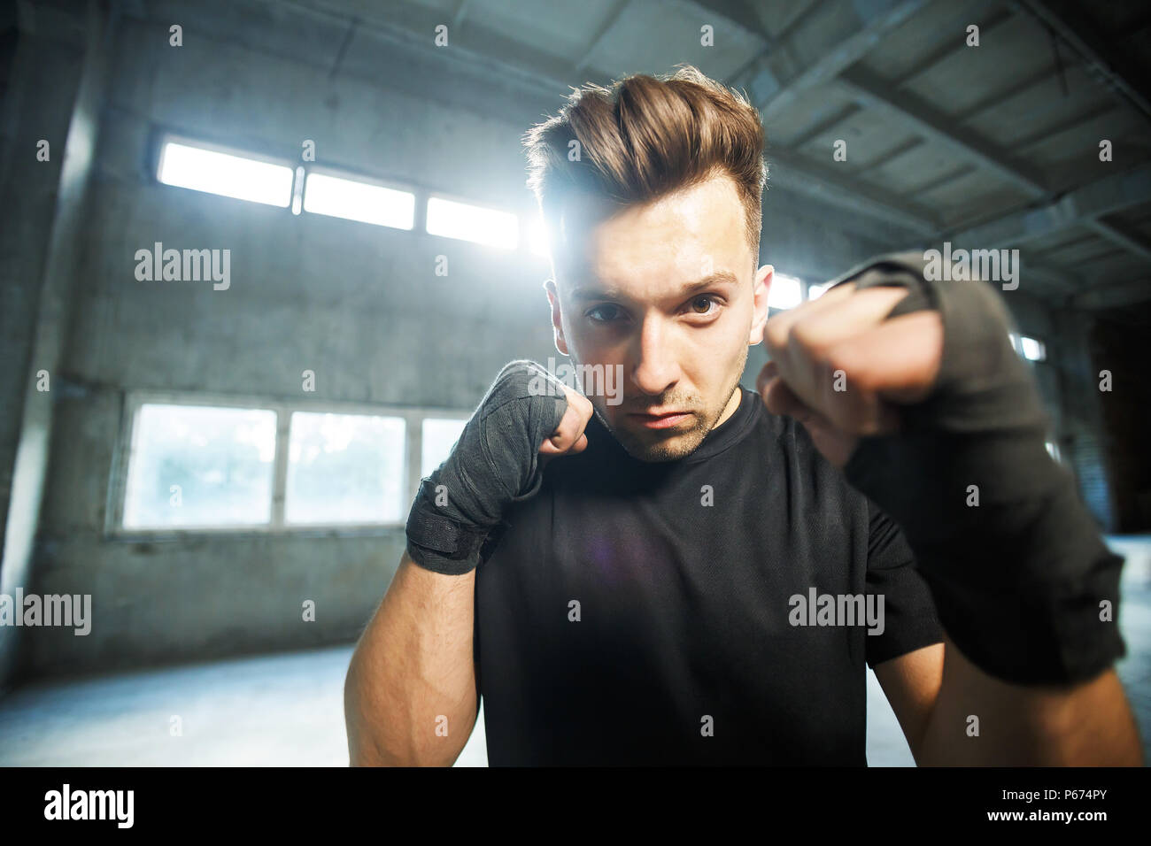 Thai boxer stay in position, fists with black bandages around at empty industrial dusty place - Stock Image
