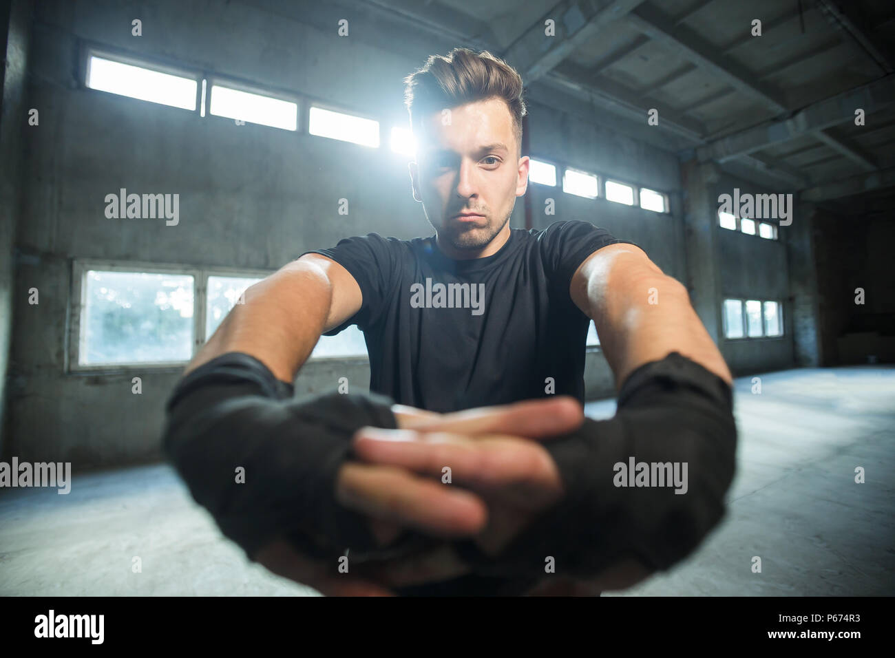 Thai boxer dressed in black t-shirt stay in position, fists with black bandages around at empty industrial dusty place - Stock Image